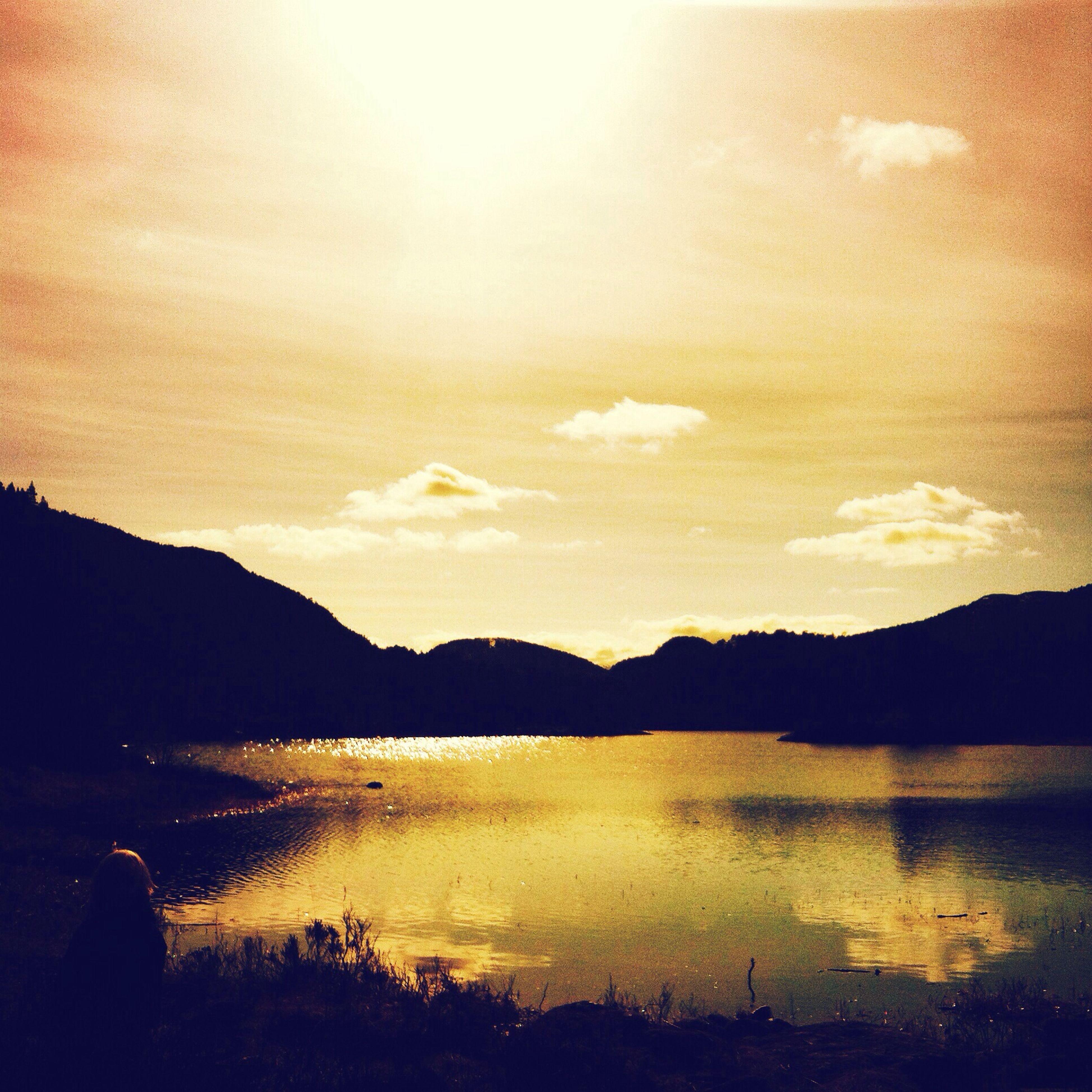 water, mountain, sunset, silhouette, lake, tranquil scene, scenics, tranquility, reflection, beauty in nature, mountain range, sky, sun, nature, idyllic, lakeshore, sunlight, outdoors, non-urban scene, calm