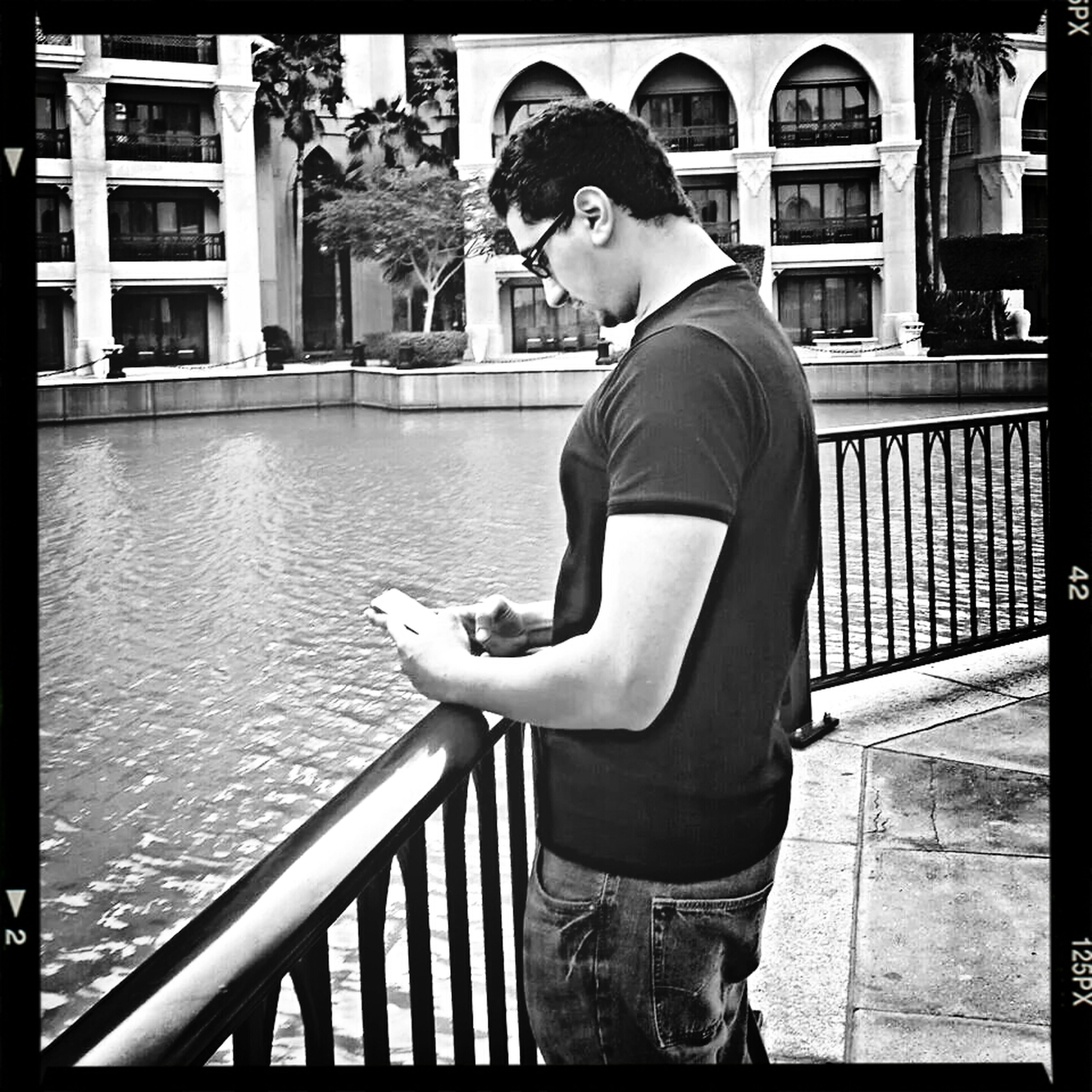 transfer print, young adult, person, lifestyles, auto post production filter, built structure, full length, architecture, casual clothing, building exterior, water, railing, leisure activity, standing, sitting, looking at camera, portrait, three quarter length