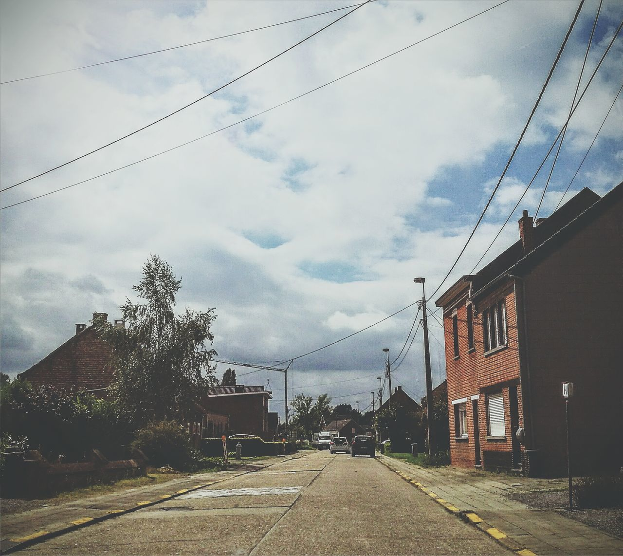 cable, sky, cloud - sky, power line, building exterior, architecture, built structure, transportation, road, outdoors, day, power supply, tree, telephone line, the way forward, street, electricity pylon, no people, nature, city