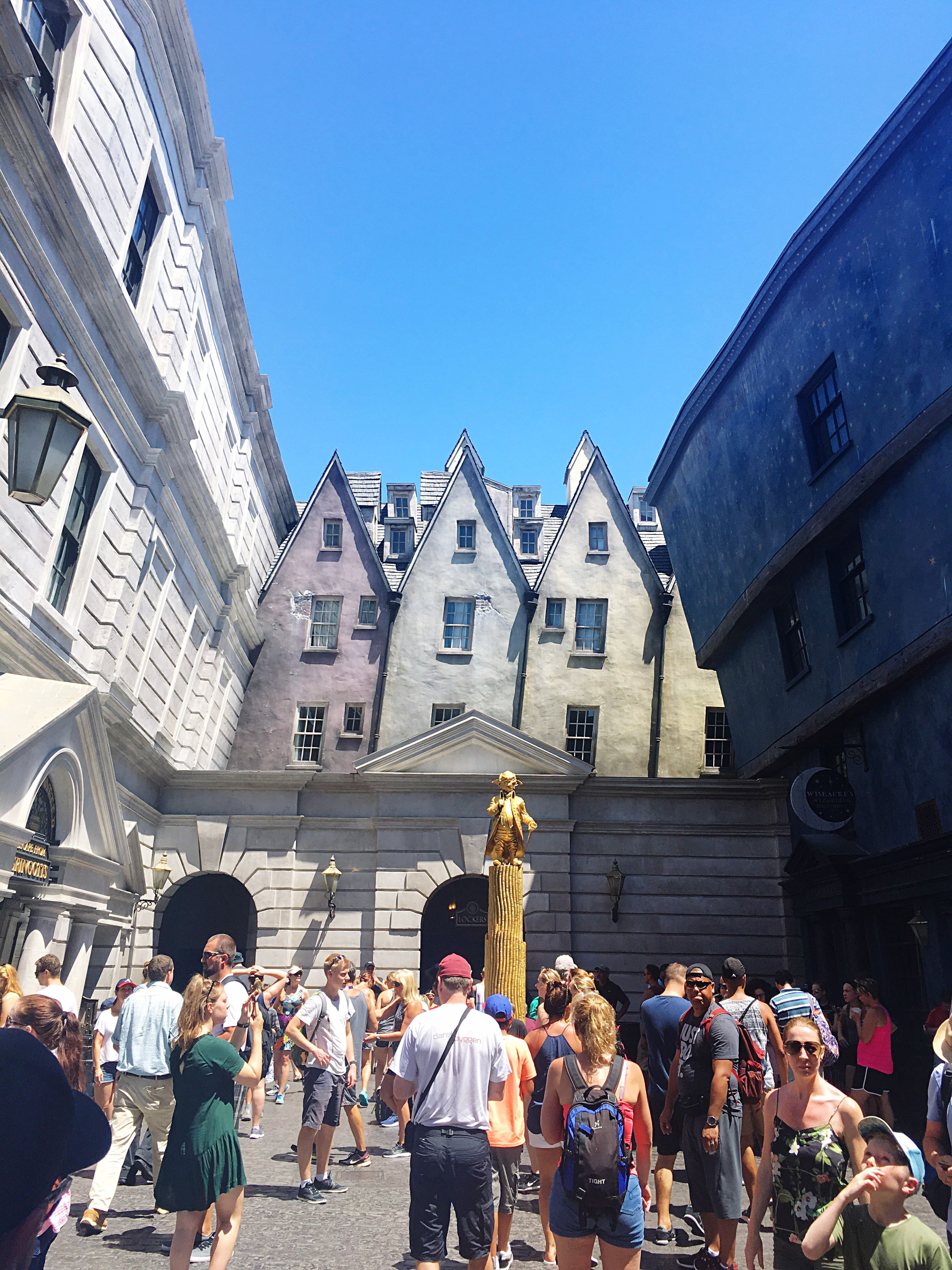 architecture, building exterior, built structure, large group of people, real people, day, outdoors, statue, men, women, sculpture, sunlight, city, city life, lifestyles, travel destinations, clear sky, sky, people