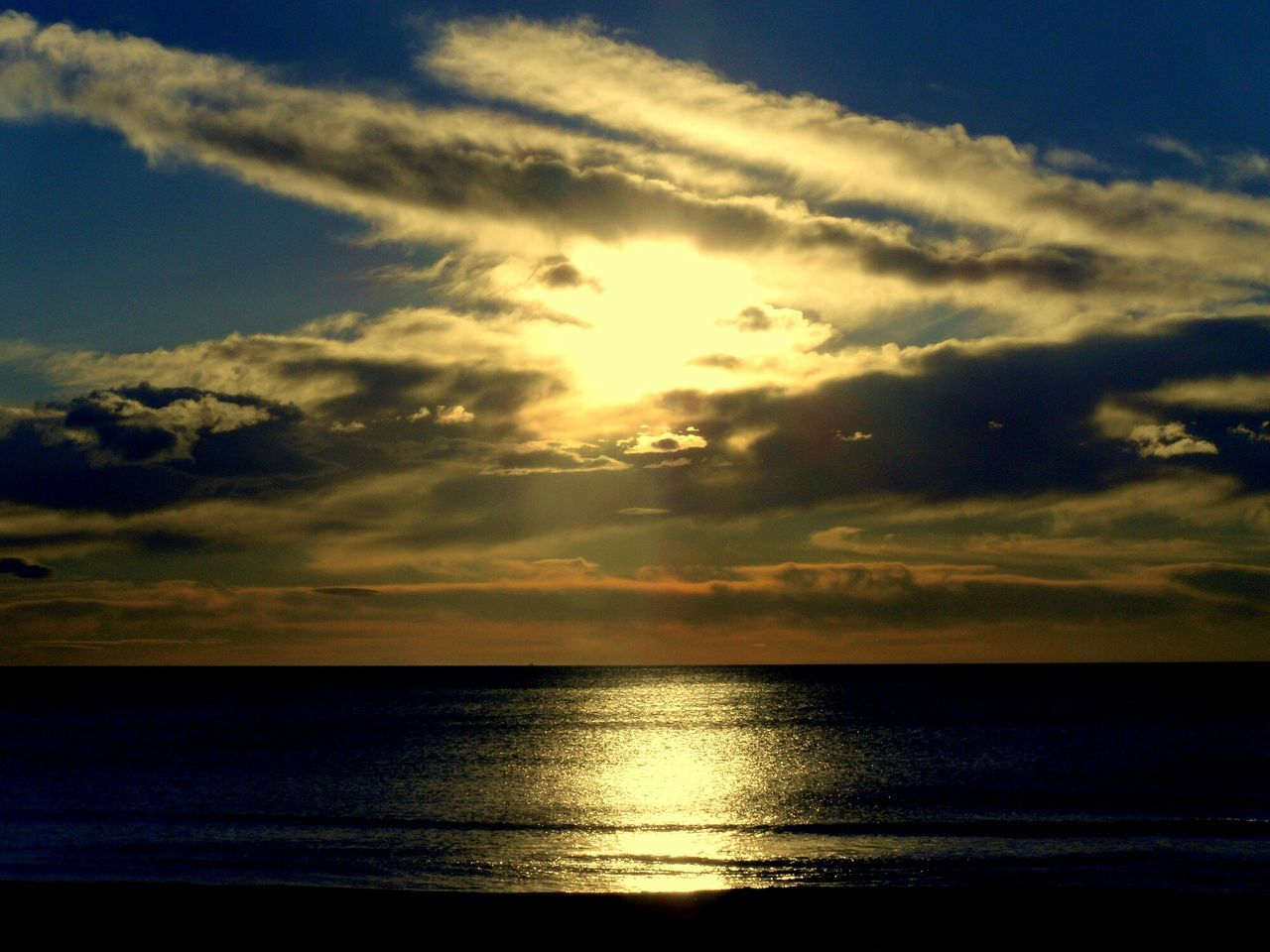 Sun Shining Through Clouds Over Sea During Dusk