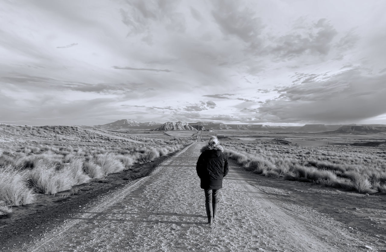 """Held in the natural park of the Bardenas Reales, where a chapter of the series """"Games of thrones"""" Cloud - Sky Cold Temperature Day Landscape Mountain One Person One Woman Only Only Women Outdoors People Rear View Sand Dune Walking"""