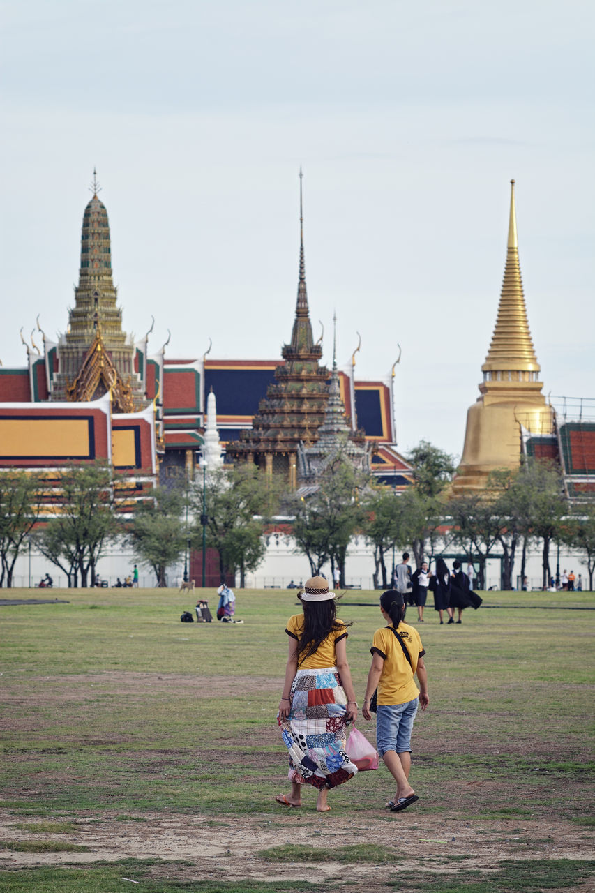 People On Field By Wat Phra Kaew Against Clear Sky