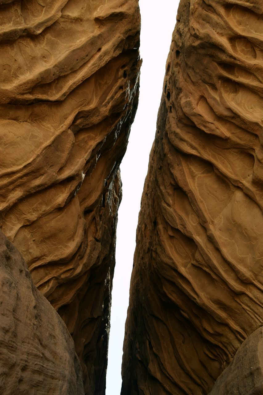 rock formation, low angle view, geology, day, nature, no people, arid climate, beauty in nature, physical geography, textured, brown, outdoors, desert, cliff, sky, close-up