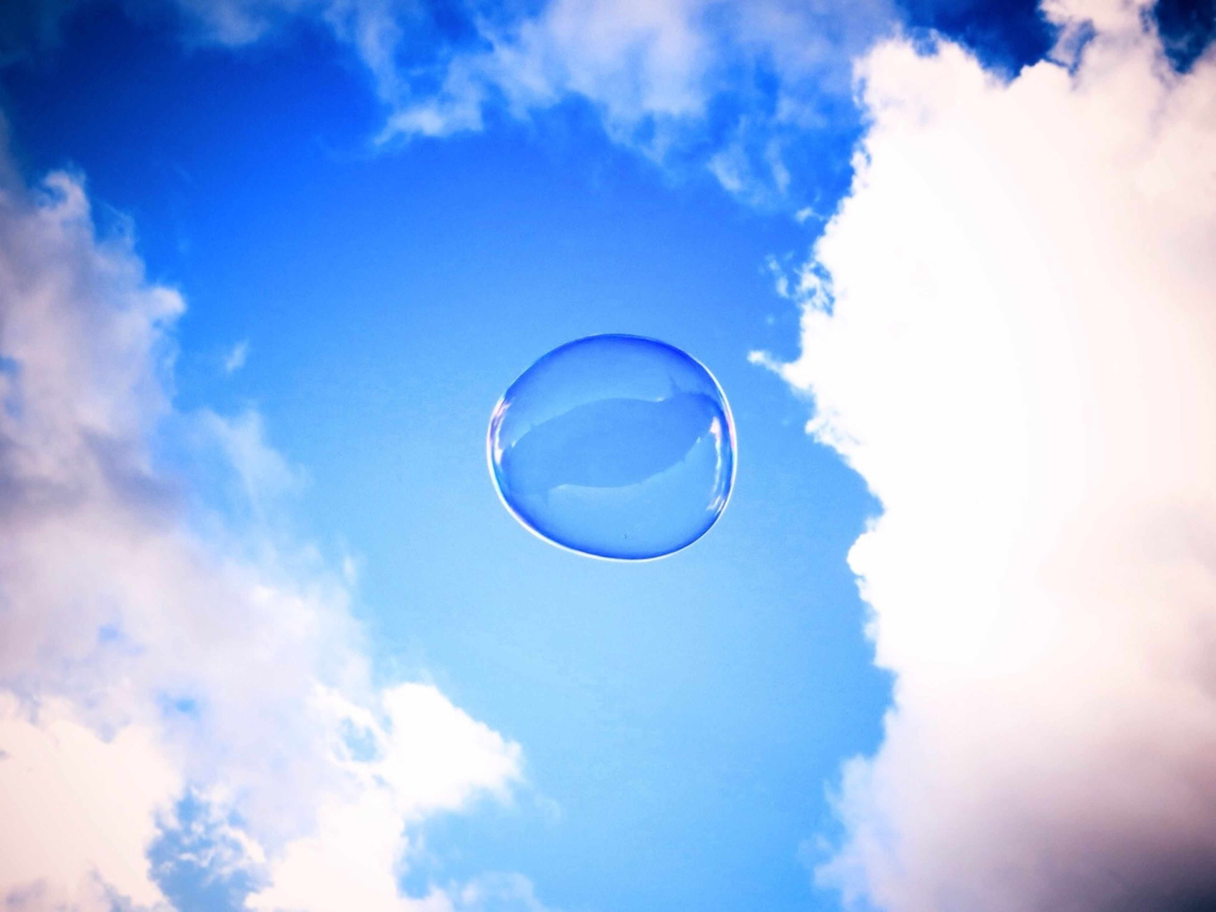 low angle view, sky, mid-air, cloud - sky, blue, circle, flying, bubble, sphere, cloud, hot air balloon, nature, beauty in nature, adventure, sport, outdoors, scenics, day, cloudy, fun