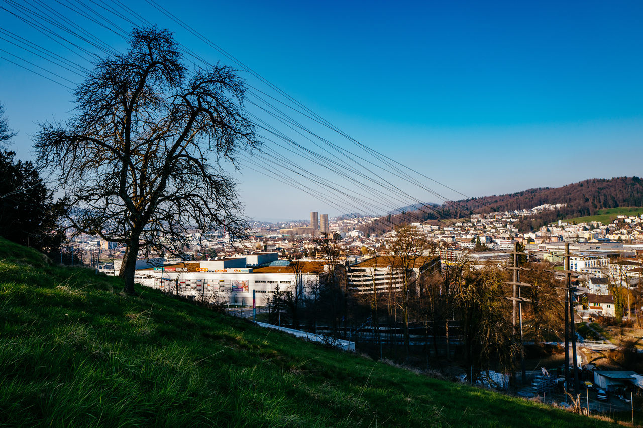 architecture, built structure, building exterior, house, tree, no people, blue, clear sky, sky, mountain, residential building, cable, outdoors, grass, landscape, day, town, nature, city, electricity pylon