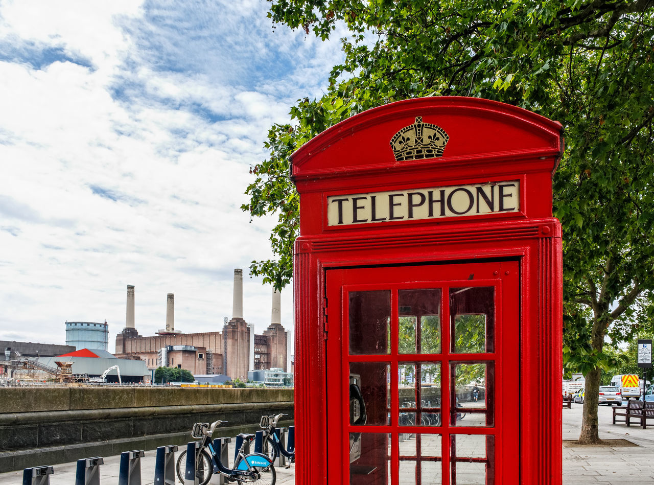 Architecture Battersea Power Station Building Exterior Built Structure City Communication Day London No People Outdoors Pay Phone Power Public Mailbox Red Sky Telephone Telephone Booth Text Tree