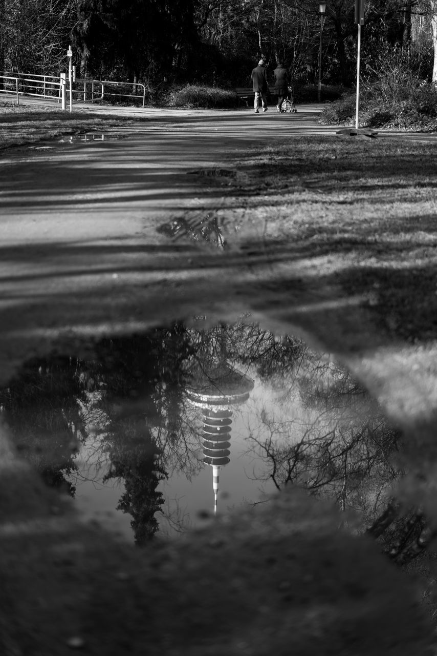 Reflection Of Tower In Puddle On Street