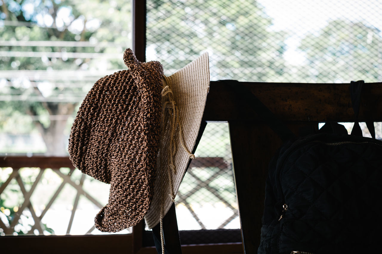 Two wide brim hats on the back of a wooden chair Accessories Airy Brown Chair Close-up Collection Copy Space Cream Day Fashion Girl Glass - Material Hanging Hat Home Indoors  Interior Order Outing Spaces Summer Wide Brim Hat Woman