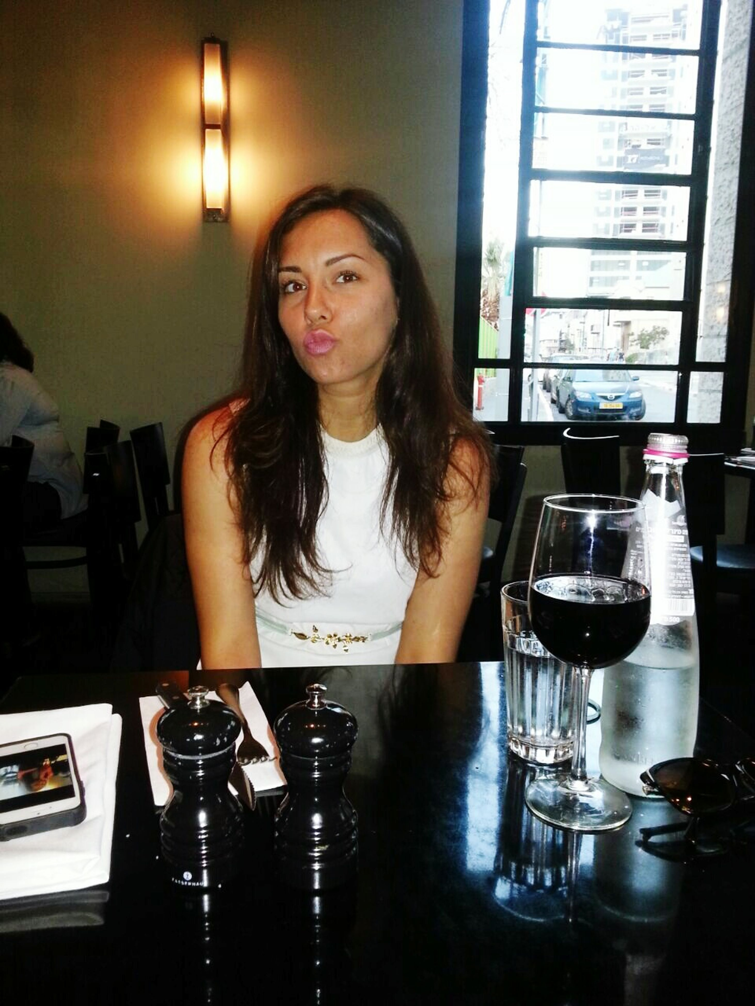 indoors, young adult, lifestyles, person, front view, leisure activity, casual clothing, drink, young women, looking at camera, food and drink, table, waist up, holding, portrait, sitting, wireless technology, restaurant