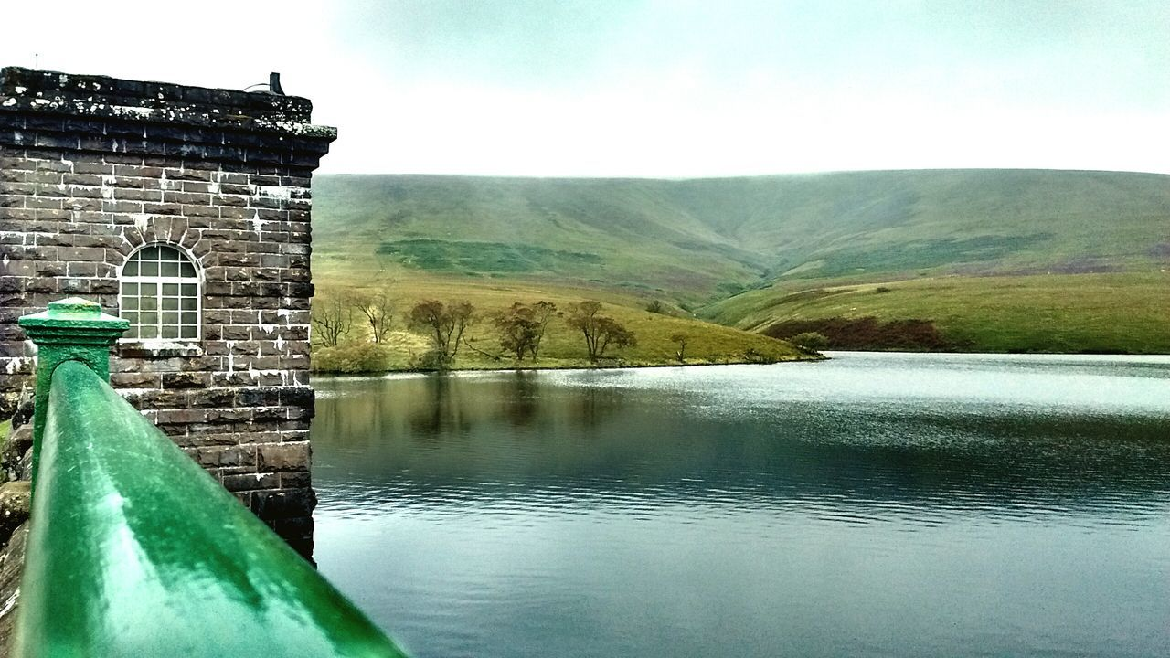 water, architecture, no people, built structure, outdoors, day, sky, history, lake, green color, travel destinations, nature, mountain, building exterior, beauty in nature, close-up