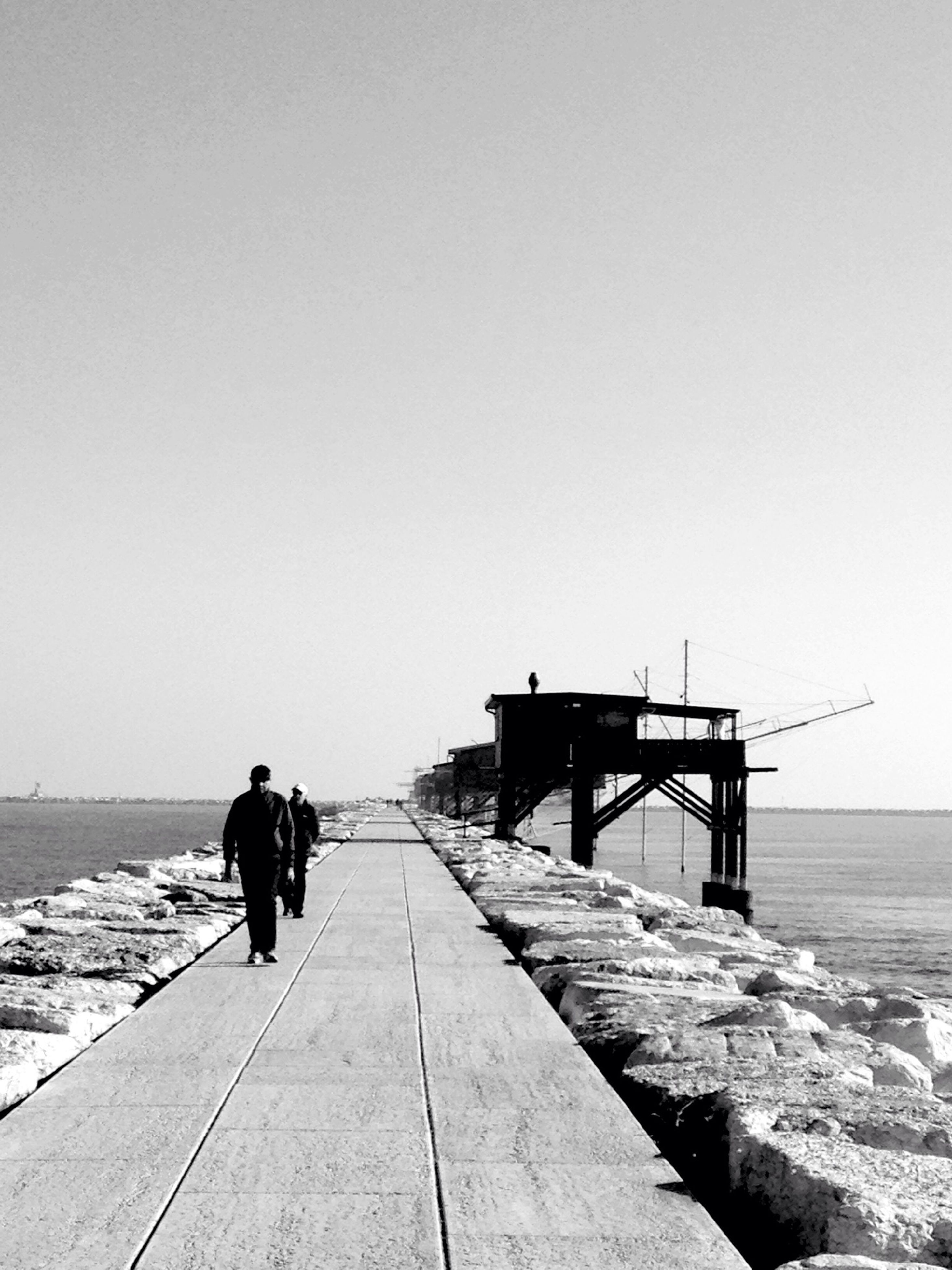 clear sky, sea, the way forward, copy space, water, horizon over water, pier, men, jetty, tranquil scene, tranquility, rear view, full length, nature, lifestyles, transportation, scenics, diminishing perspective