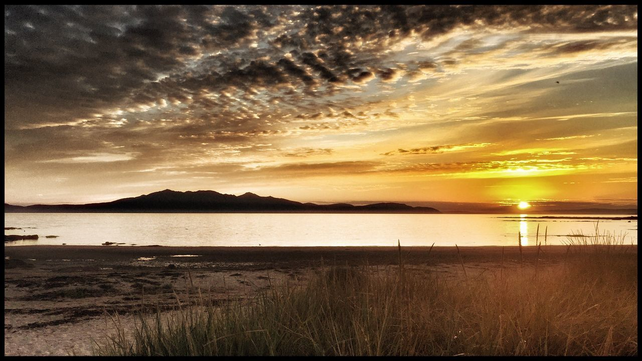 sunset, water, scenics, nature, tranquil scene, beauty in nature, tranquility, sea, sky, silhouette, sun, no people, reflection, travel destinations, landscape, grass, outdoors, beach, mountain, horizon over water