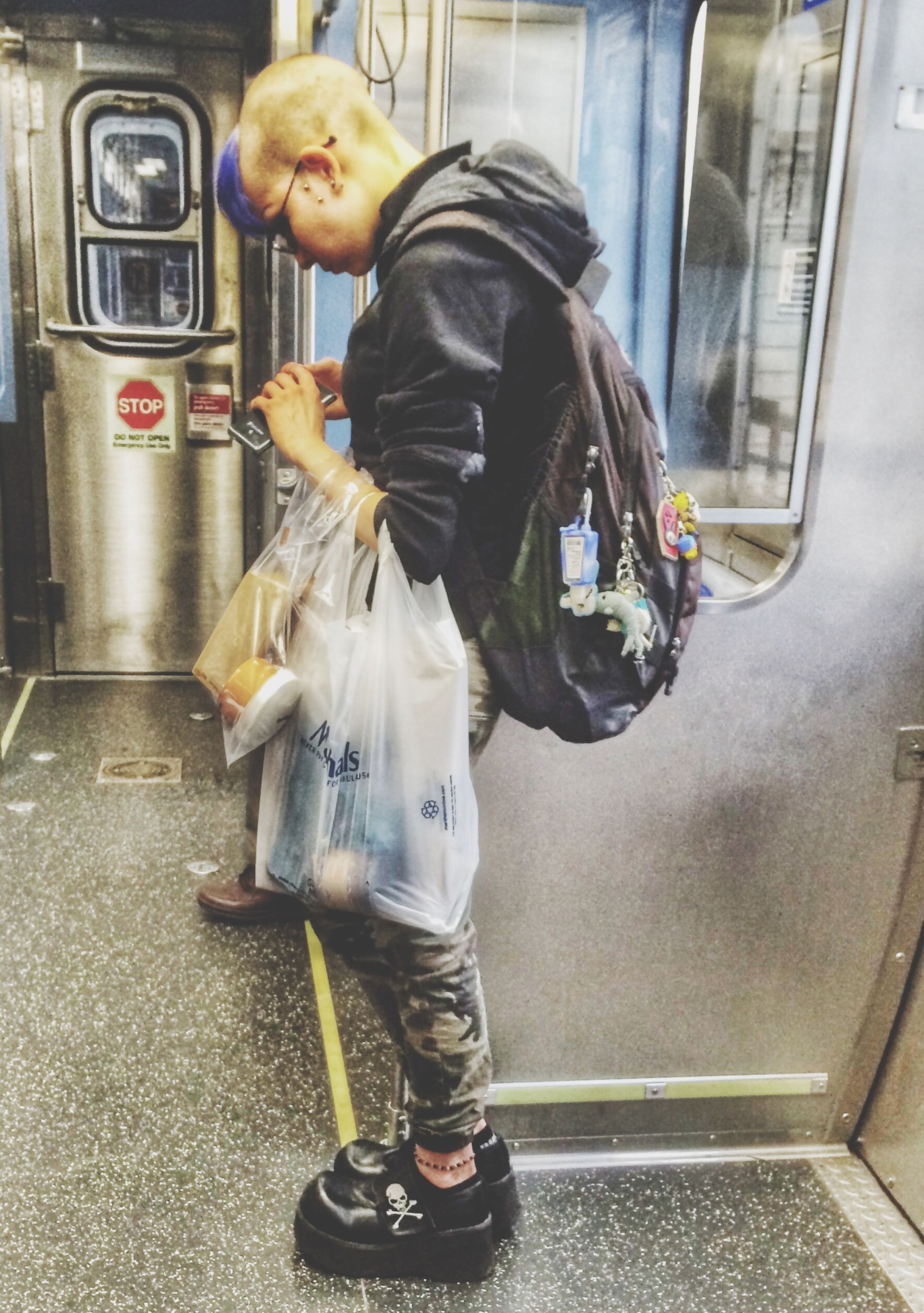 full length, indoors, casual clothing, lifestyles, leisure activity, men, holding, transportation, person, mode of transport, sitting, childhood, three quarter length, standing, front view, boys, communication, street