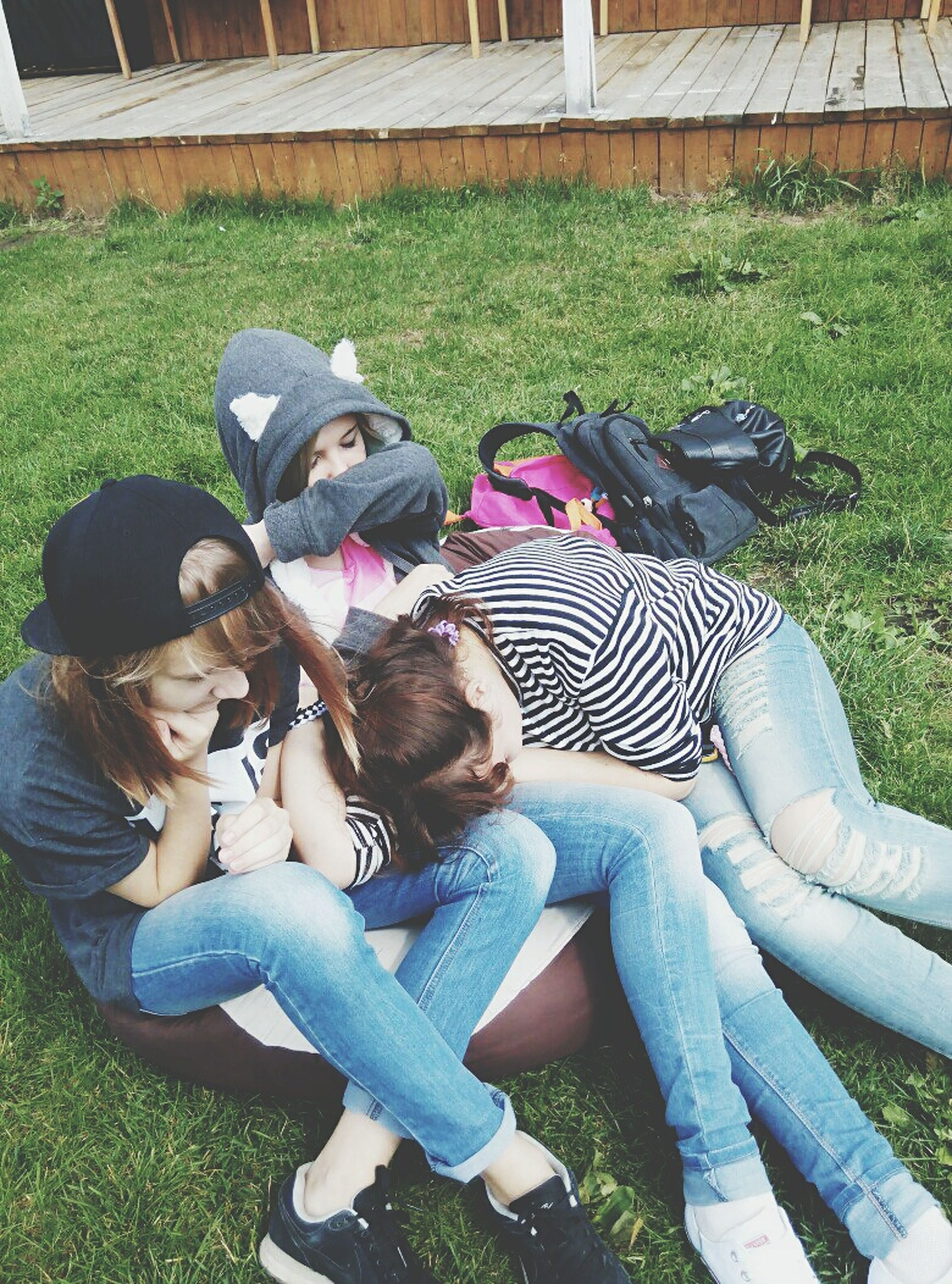 grass, lifestyles, leisure activity, sitting, togetherness, relaxation, casual clothing, person, bonding, lying down, childhood, park - man made space, young adult, full length, young women, elementary age, girls