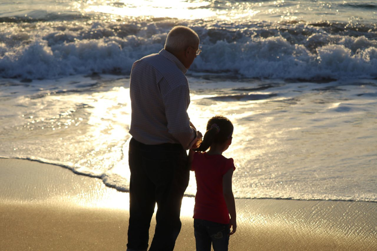 Rear View Of Man With Granddaughter Standing On Shore At Beach During Sunset