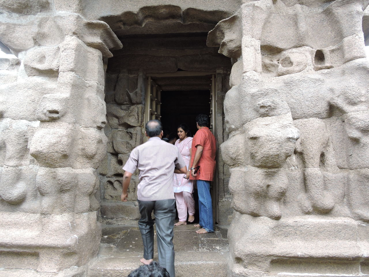 ancient, architecture, built structure, history, old ruin, men, archaeology, ancient civilization, carving - craft product, travel destinations, travel, rock - object, statue, real people, sculpture, building exterior, day, rear view, bas relief, outdoors, vacations, two people, women, full length, adult, people, sky, adults only