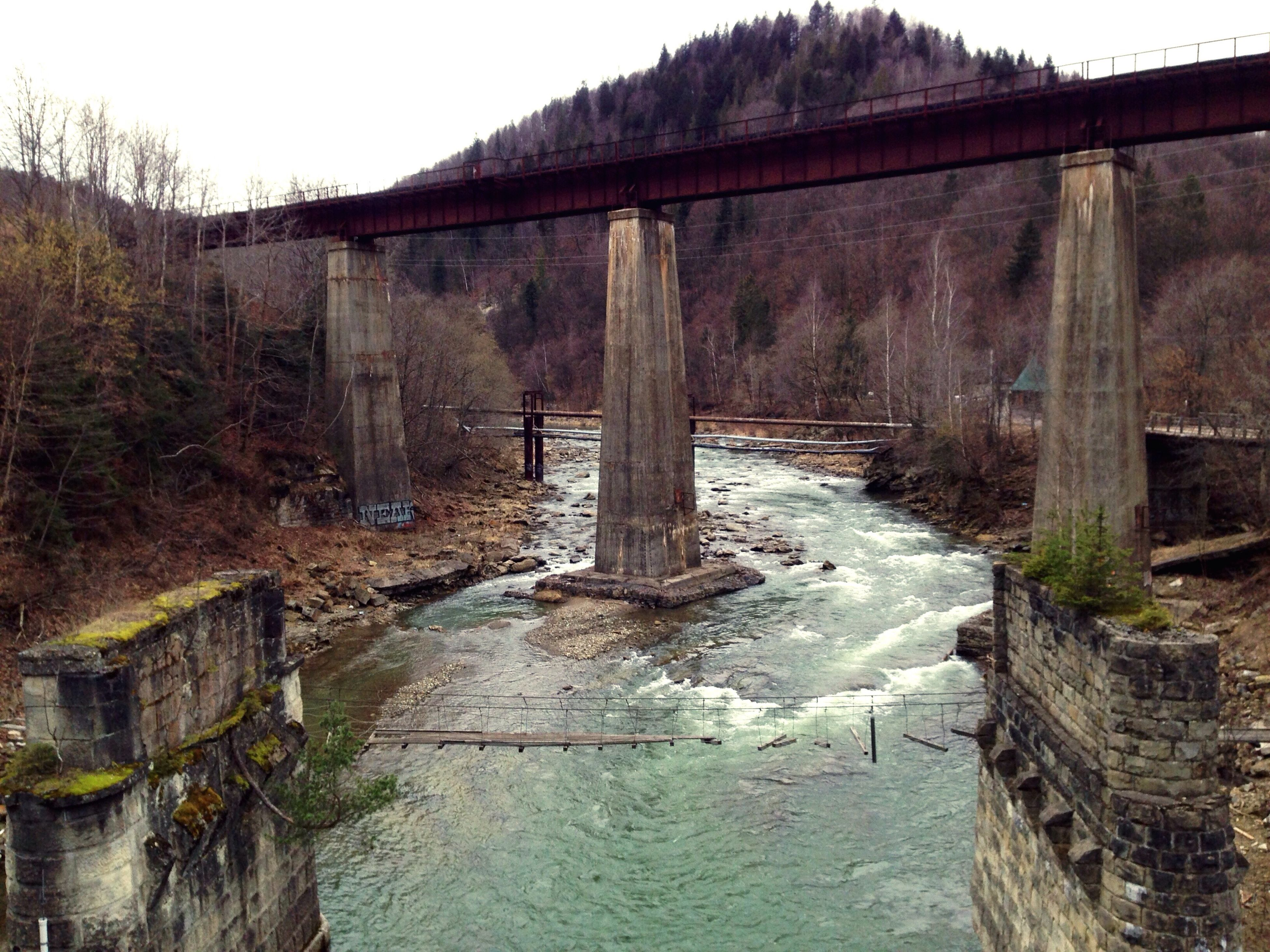 architecture, built structure, building exterior, water, bridge - man made structure, connection, arch, clear sky, sky, tree, mountain, river, bridge, stone wall, rock - object, day, old, old ruin, outdoors, house