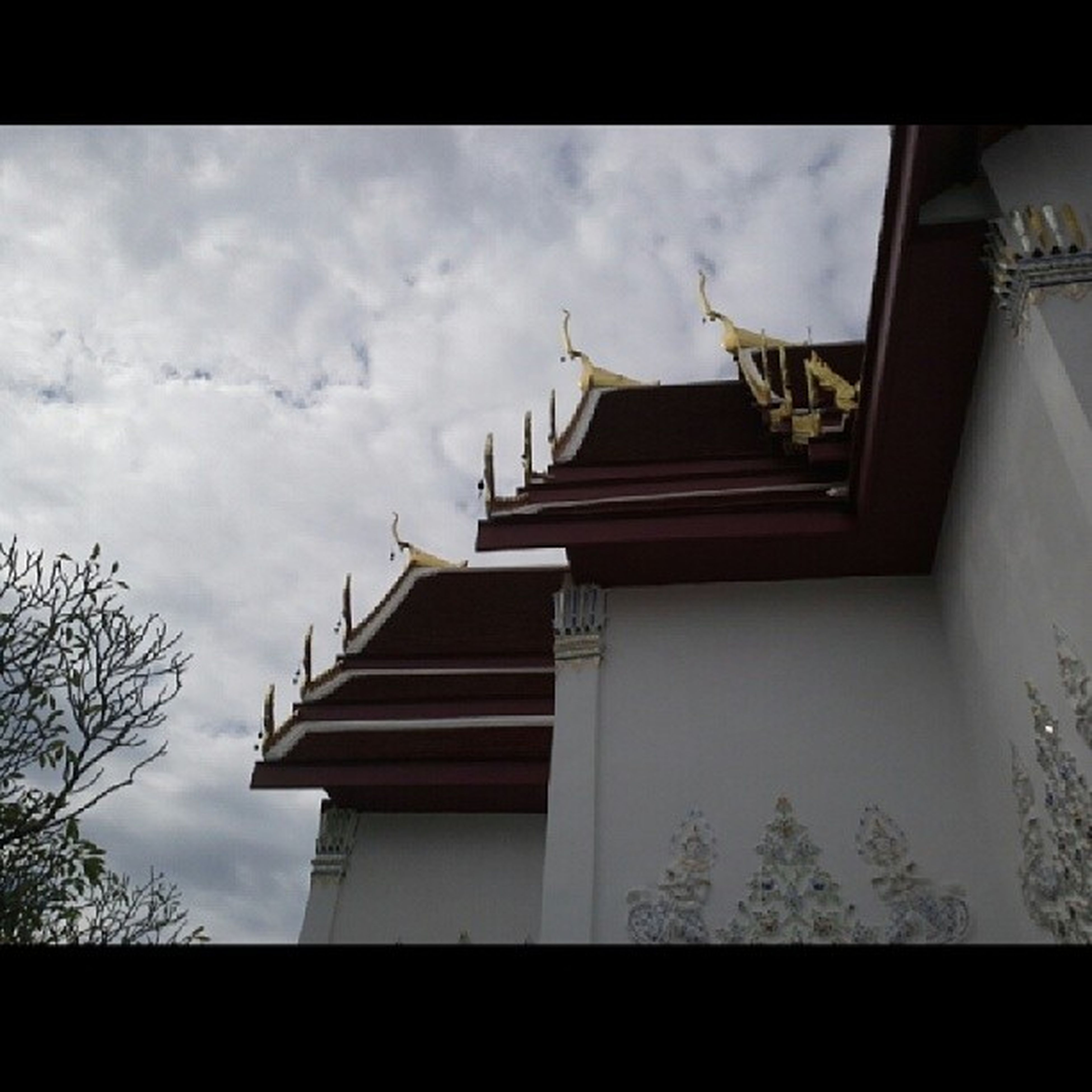 architecture, built structure, building exterior, low angle view, sky, cloud - sky, roof, place of worship, auto post production filter, house, cloud, religion, transfer print, spirituality, building, cloudy, high section, residential structure, no people, day