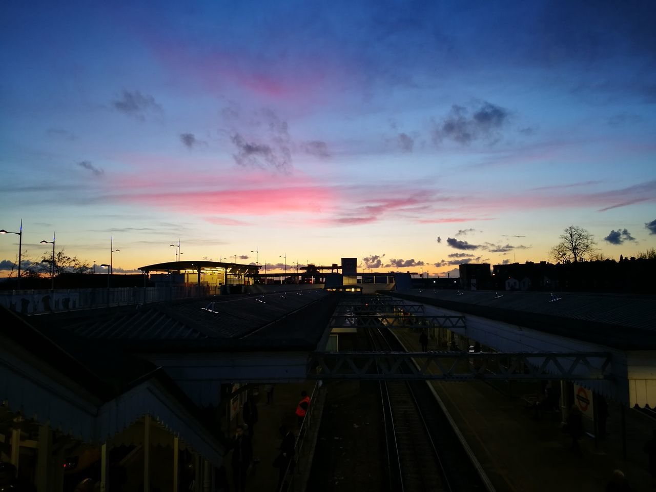 sunset, sky, transportation, built structure, rail transportation, railroad track, architecture, public transportation, high angle view, cloud - sky, building exterior, city, silhouette, outdoors, no people, nature, day