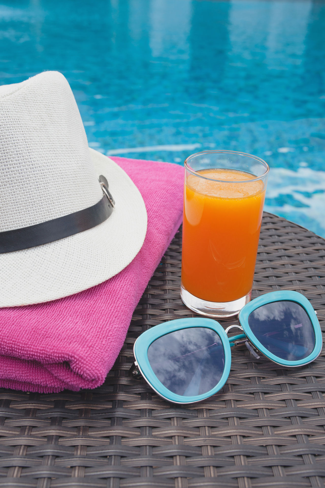 Close-up Day Drink Drinking Glass Drinking Straw Eyeglasses  Freshness No People Orange Juice  Outdoors Refreshment Still Life Summer Sun Hat Sunglasses Swimming Pool Vacations Water