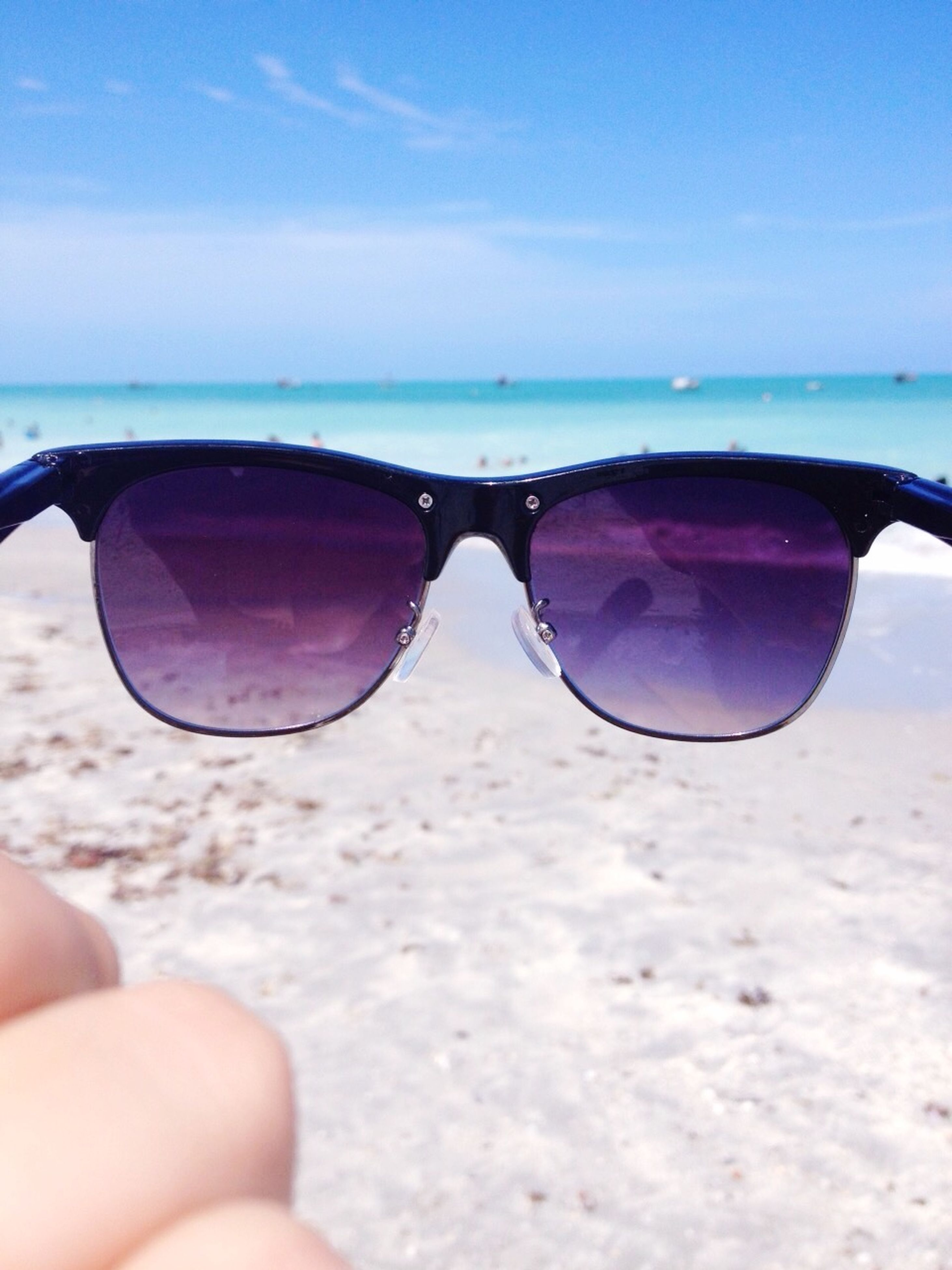 sea, beach, person, water, sky, part of, horizon over water, holding, cropped, sunglasses, close-up, shore, sand, blue, leisure activity, reflection, transparent