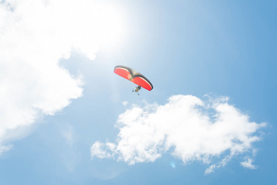 Enjoying flying action. Action Adventure Adventurous Cloud - Sky Day Extreme Sports Fly Flying Lifestyles Low Angle View Mid-air One Person Outdoors Parachute Paragliding People Red Sky Sport