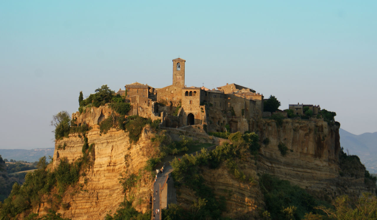 The afternoon sun lights up the ancient Italian town of Civita di Bagnoreggio in a golden glow. Ancient City Ancient Civilization Architecture Bridge Built Structure Civita Di Bagnoregio Day History Italian Italy Medieval Outdoors Sky Sunlight Sunlight And Shadow Tower Travel Destinations Tufa