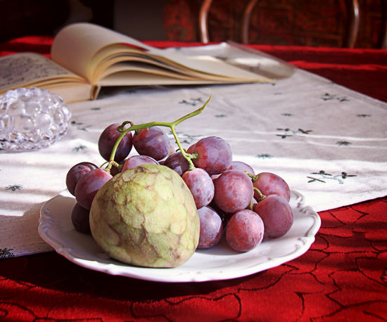 Indoor still life, a fruit plate of cherimoya and purple grapes on the tablecloth with blurred book and glass decoration in background Blurred Background Book Cherimoya Close-up Comfortable Cozy Place Day Food Freshness Fruit Grapes Healthy Eating Lifestyle Nature No People Organic Quality Relax Room Still Life Table
