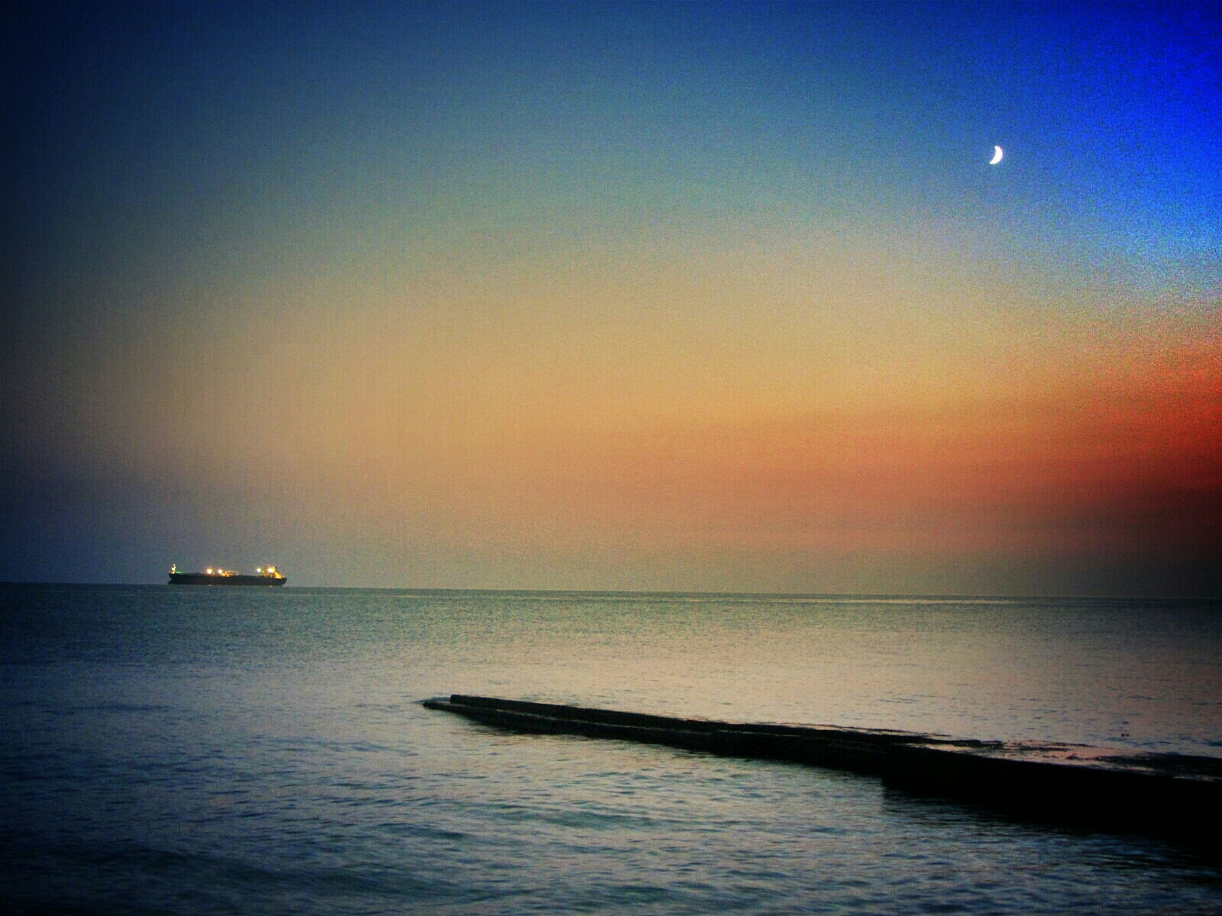 sea, water, horizon over water, sunset, tranquil scene, scenics, tranquility, beauty in nature, waterfront, nautical vessel, nature, idyllic, copy space, sky, transportation, boat, orange color, seascape, clear sky, silhouette