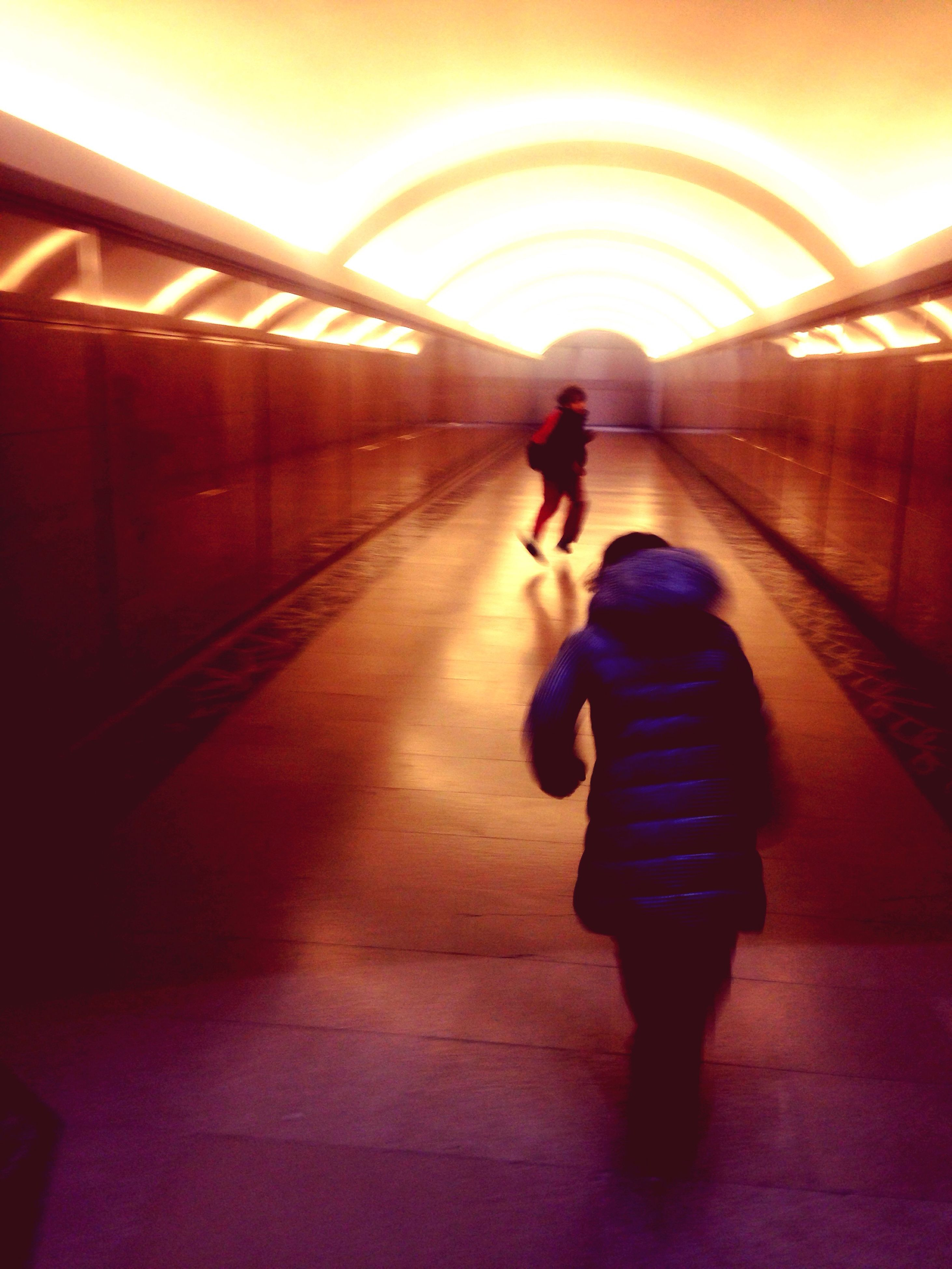 full length, indoors, lifestyles, walking, rear view, the way forward, leisure activity, architecture, built structure, standing, men, railing, tunnel, illuminated, silhouette, diminishing perspective, connection, casual clothing