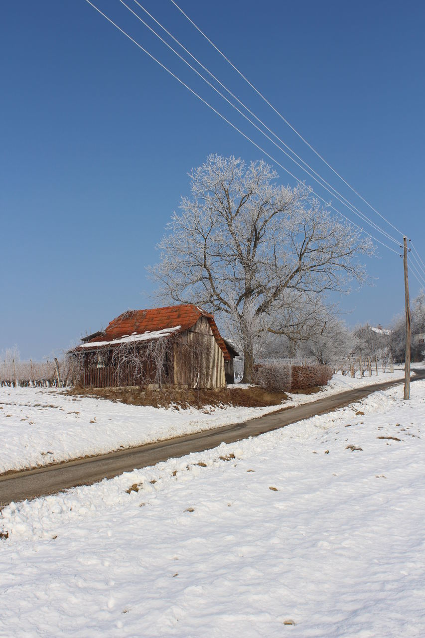 snow, winter, cold temperature, bare tree, building exterior, built structure, outdoors, day, clear sky, nature, house, no people, architecture, field, landscape, beauty in nature, tranquility, blue, tree, scenics, sky