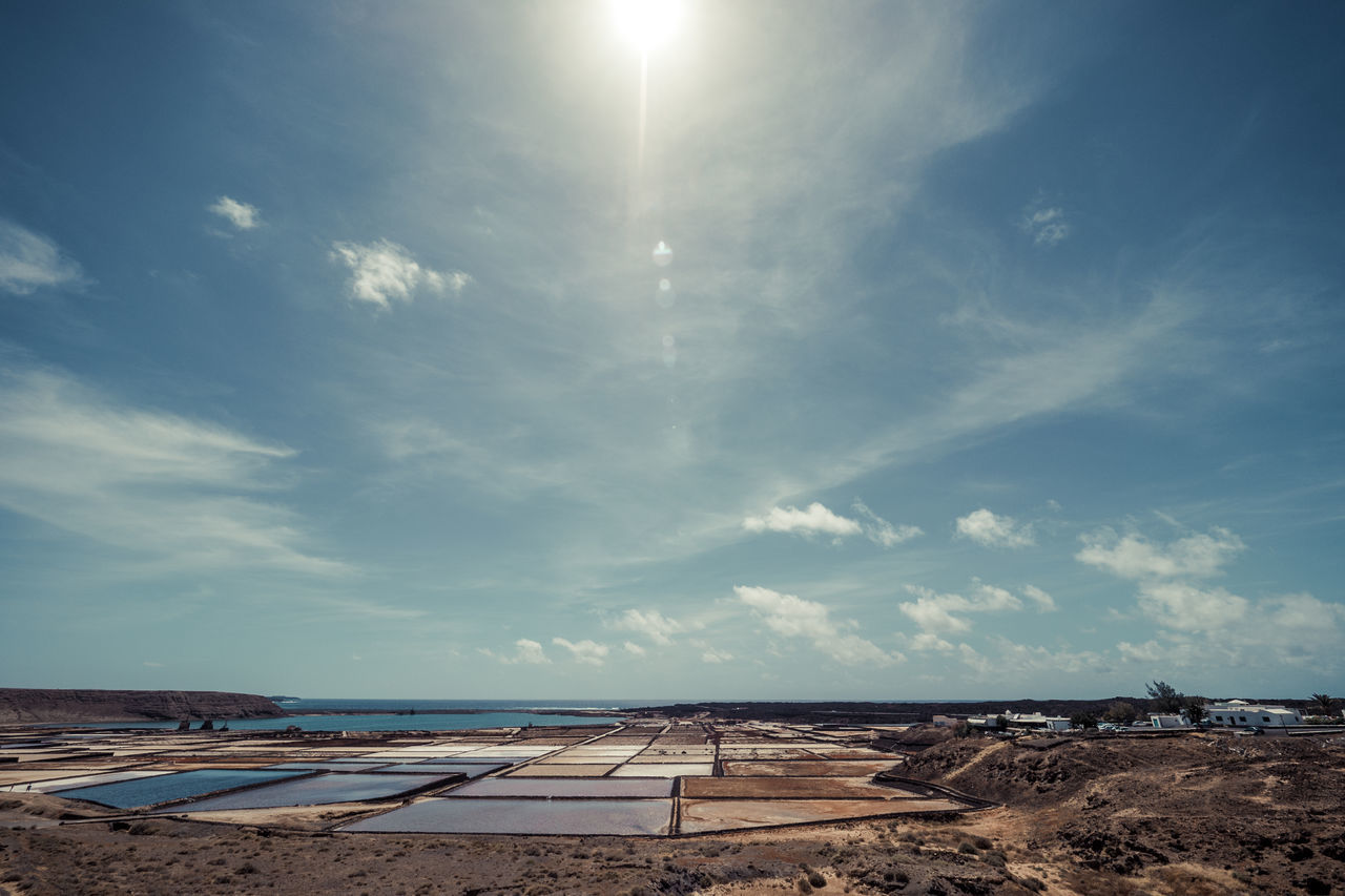 Salinas in the foreground with direct sunlight and lensflares in a cloudy sky Beauty In Nature Cloud - Sky Day Landscape Nature No People Outdoors Salt - Mineral Salt Basin Sand Scenics Sky Sunlight Tranquility
