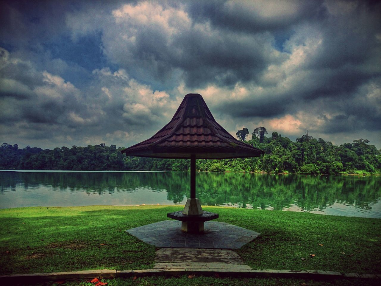 Gazebo In Front Of Lake Against Cloudy Sky At Dusk