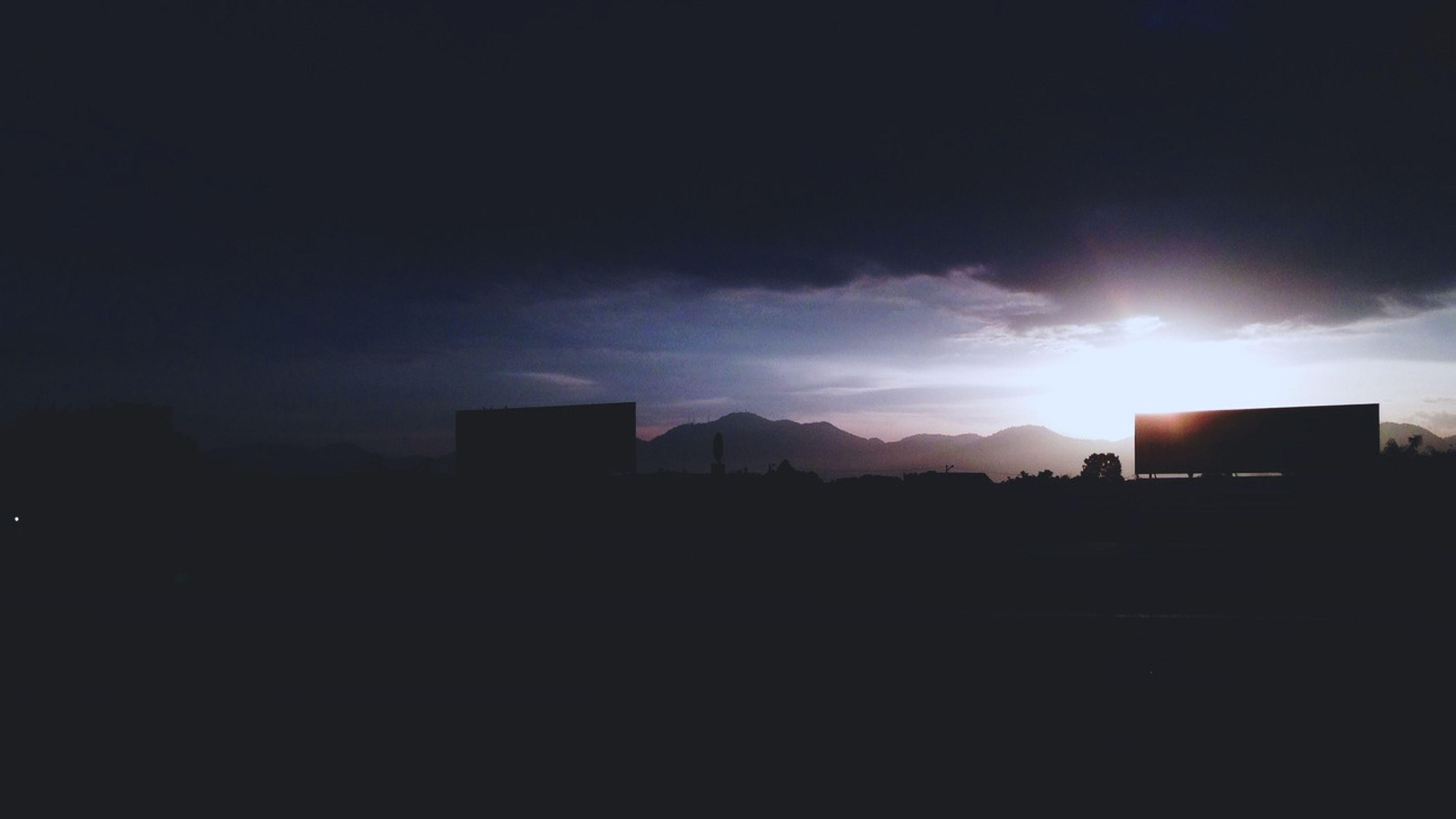 building exterior, silhouette, architecture, built structure, sky, sunset, sun, cloud - sky, city, sunlight, dark, sunbeam, cloud, cloudy, building, outdoors, no people, residential building, cityscape, scenics