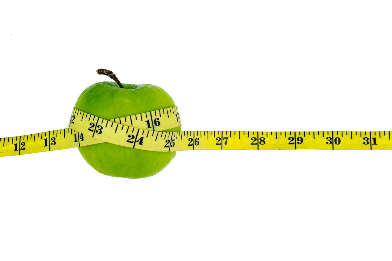 Green apple wrapped with a yellow measuring tape on white background Apple Arrangement Diet Green Green Color Healthy Eating Obesity Studio Shot Thin Vacations White Background Yellow