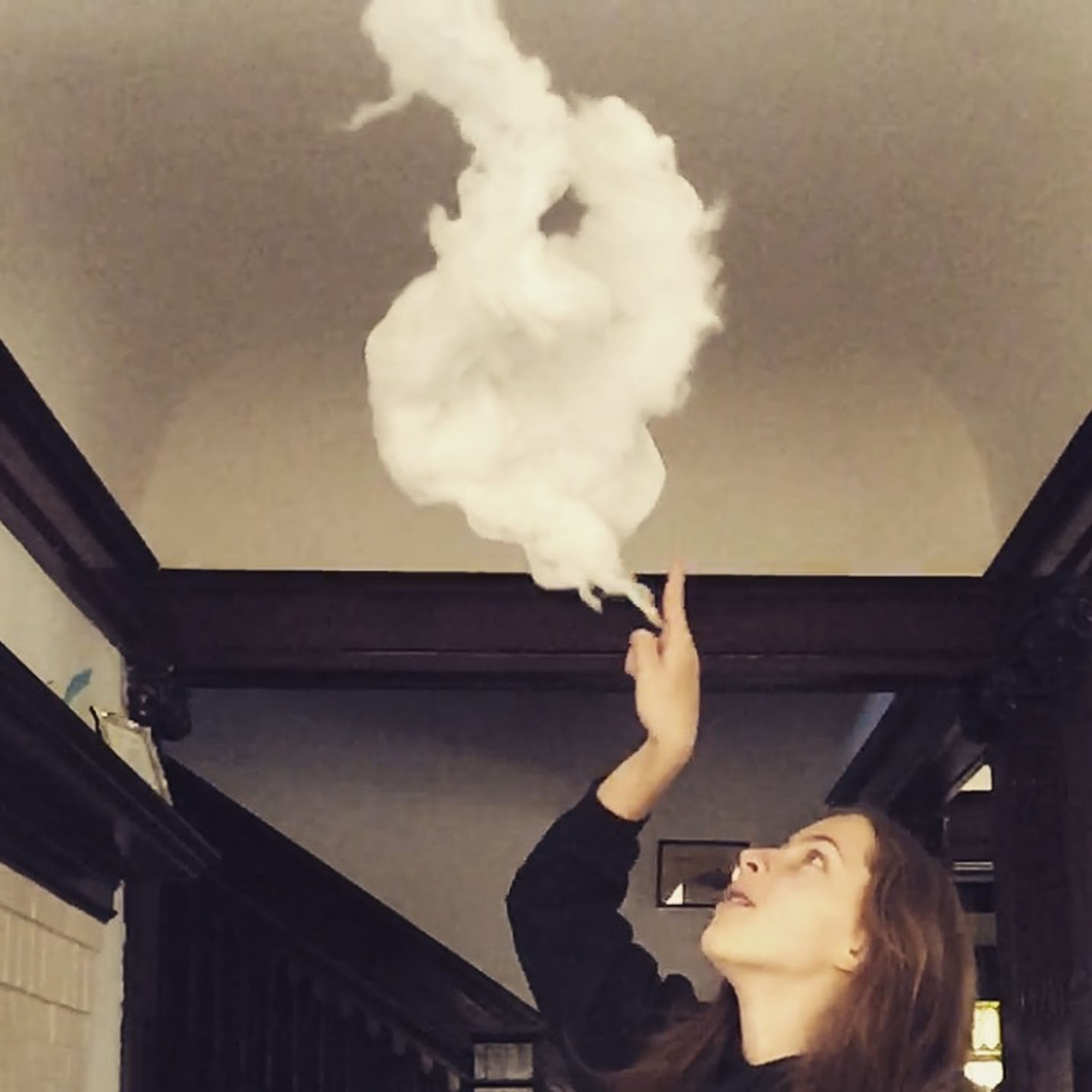 lifestyles, holding, indoors, young adult, leisure activity, person, casual clothing, architecture, young women, waist up, built structure, headshot, three quarter length, low angle view, smoke - physical structure, front view, human representation, standing