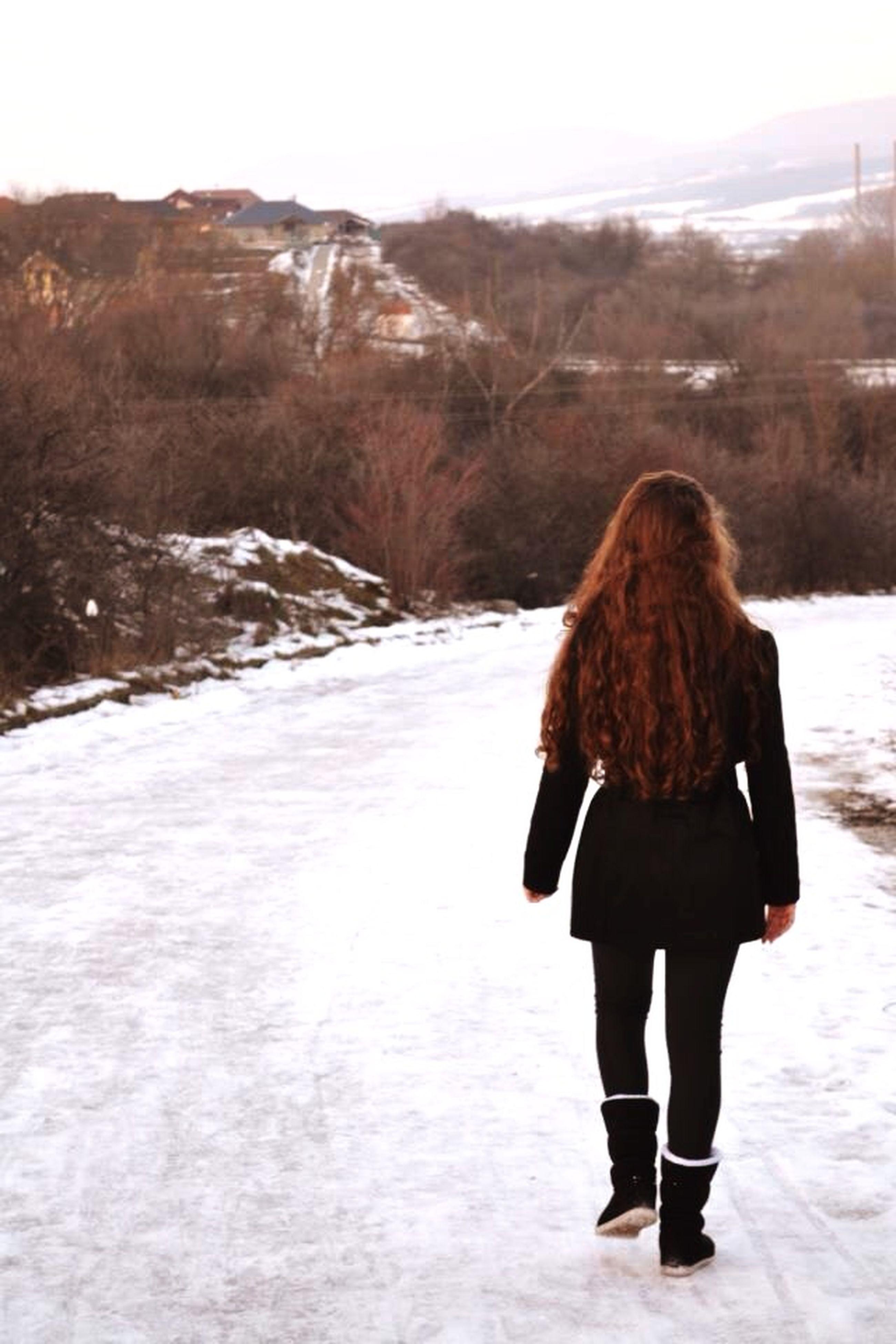 rear view, lifestyles, water, leisure activity, standing, full length, tranquil scene, winter, snow, tranquility, scenics, cold temperature, nature, beauty in nature, person, vacations, walking, mountain