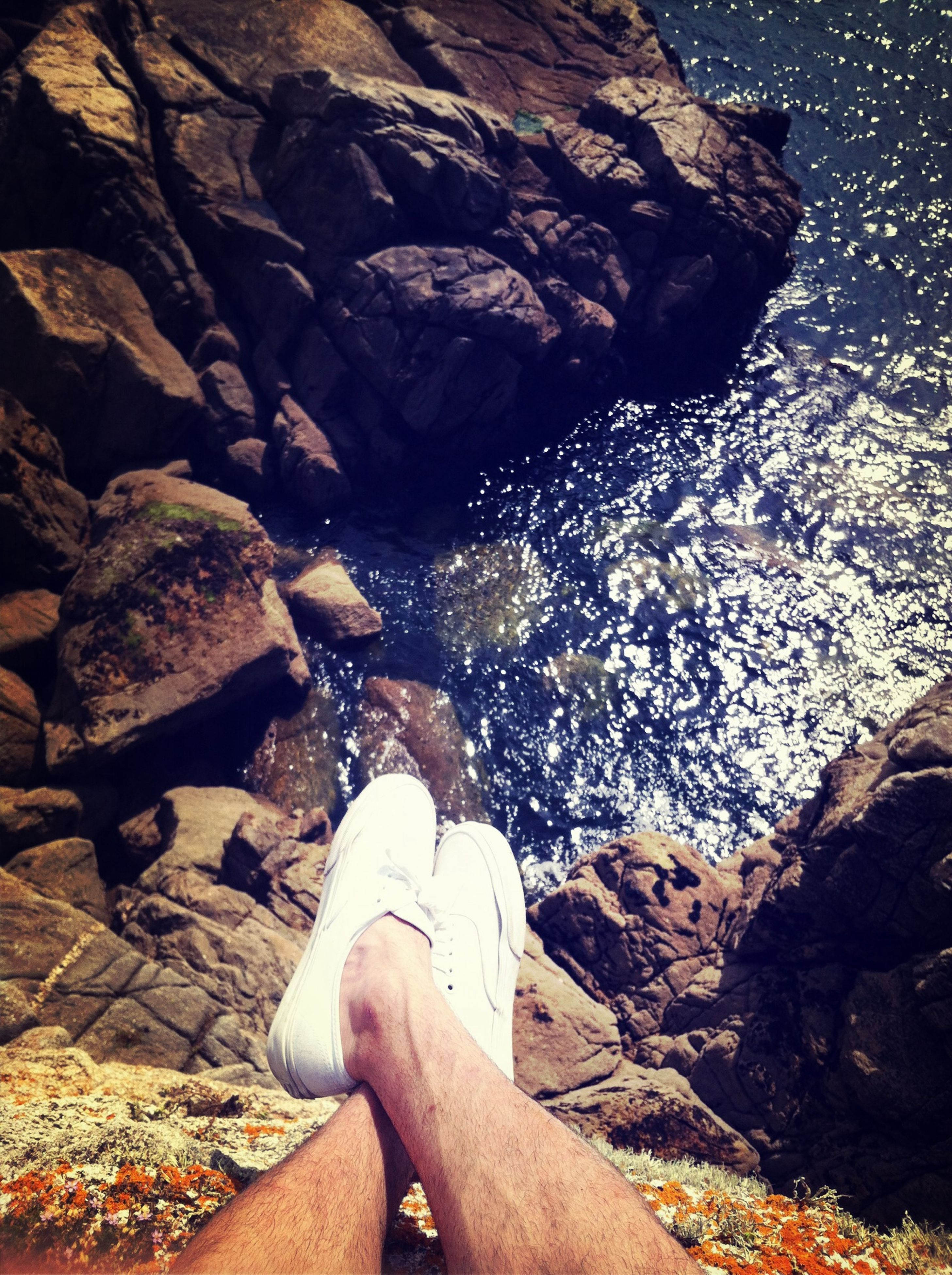 water, low section, person, personal perspective, rock - object, sea, lifestyles, human foot, high angle view, leisure activity, stone - object, shoe, part of, beach, nature, standing, sunlight