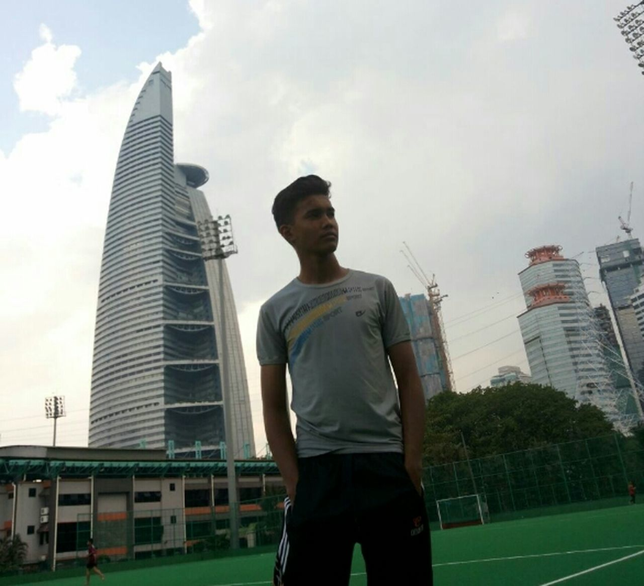 architecture, skyscraper, young adult, city, built structure, one person, casual clothing, building exterior, young men, sky, outdoors, day, low angle view, real people, standing, sport, lifestyles, men, one young man only, sportsman, one man only, only men, urban skyline, cityscape, athlete, adult, adults only, people