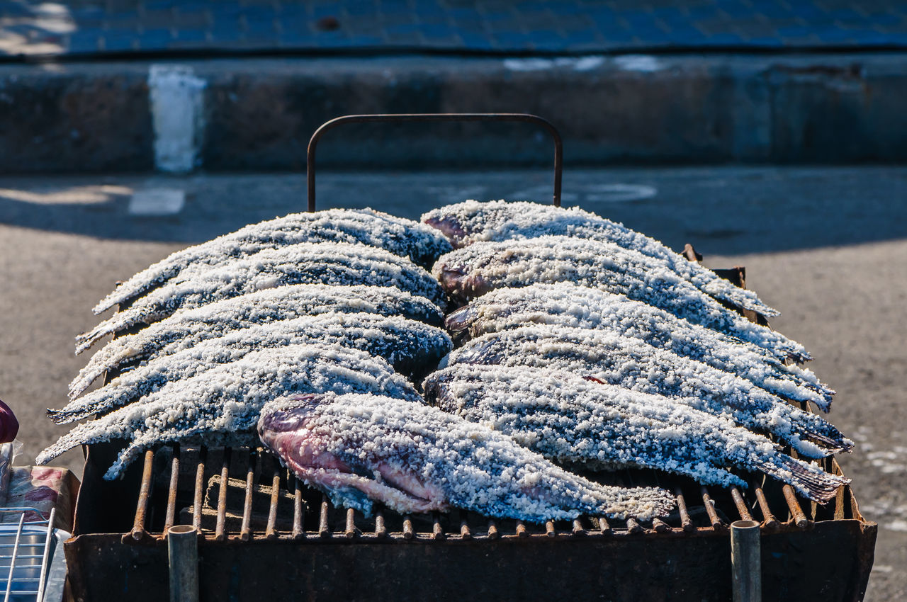 High Angle View Of Fish Covered With Salt On Barbecue At Market Stall
