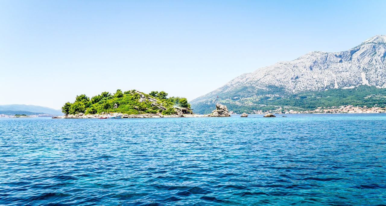 The island Beauty In Nature Blue Clear Sky Day Idyllic Island, Landscape Mountain Nature No People Outdoors Relaxation Scenics Sea Sky Tranquil Scene Tranquility Tree Water Yachting