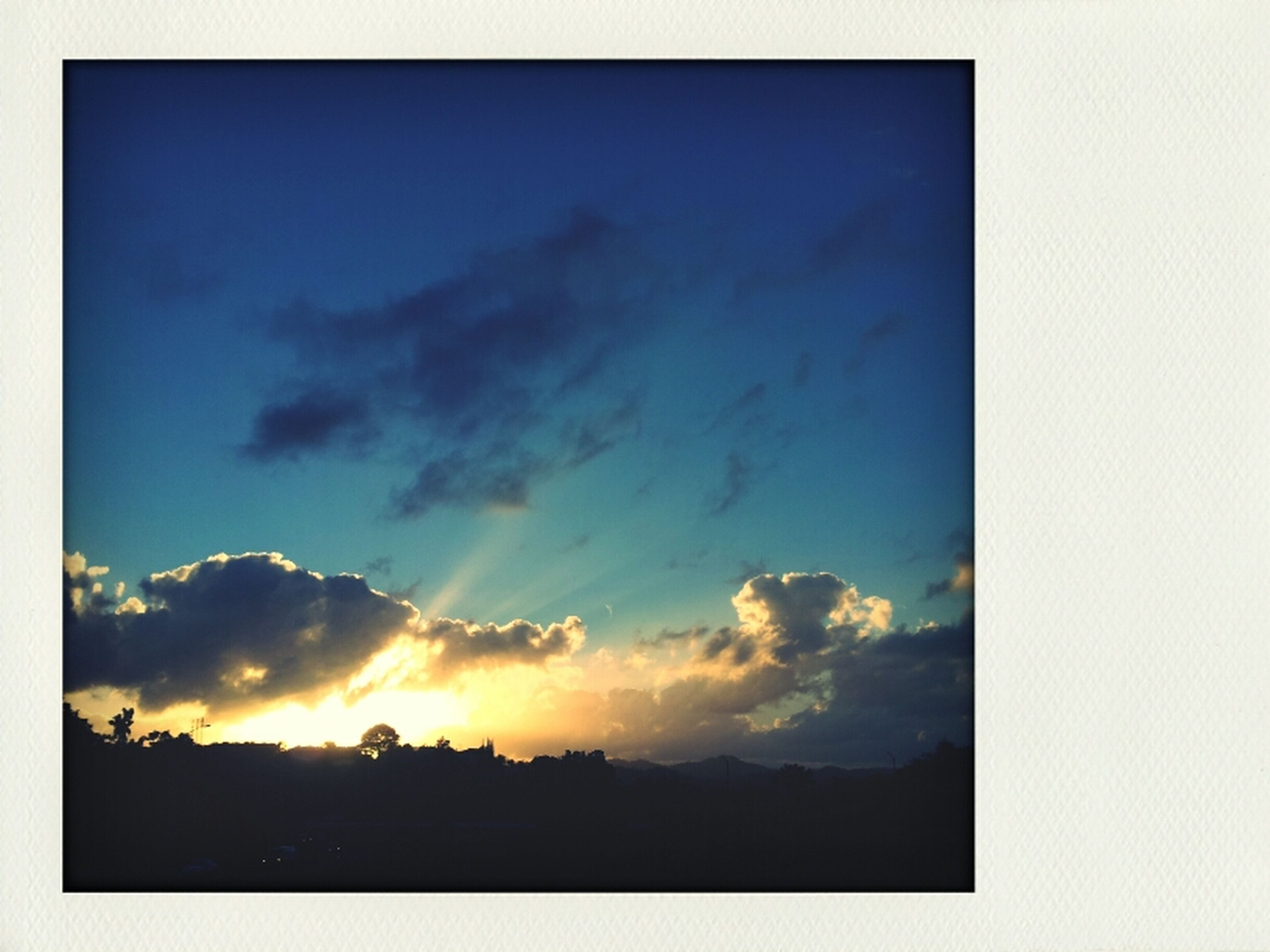 transfer print, sky, cloud - sky, silhouette, sunset, auto post production filter, scenics, beauty in nature, cloud, cloudy, tranquil scene, tranquility, nature, low angle view, idyllic, outdoors, sunlight, dramatic sky, sun, building exterior
