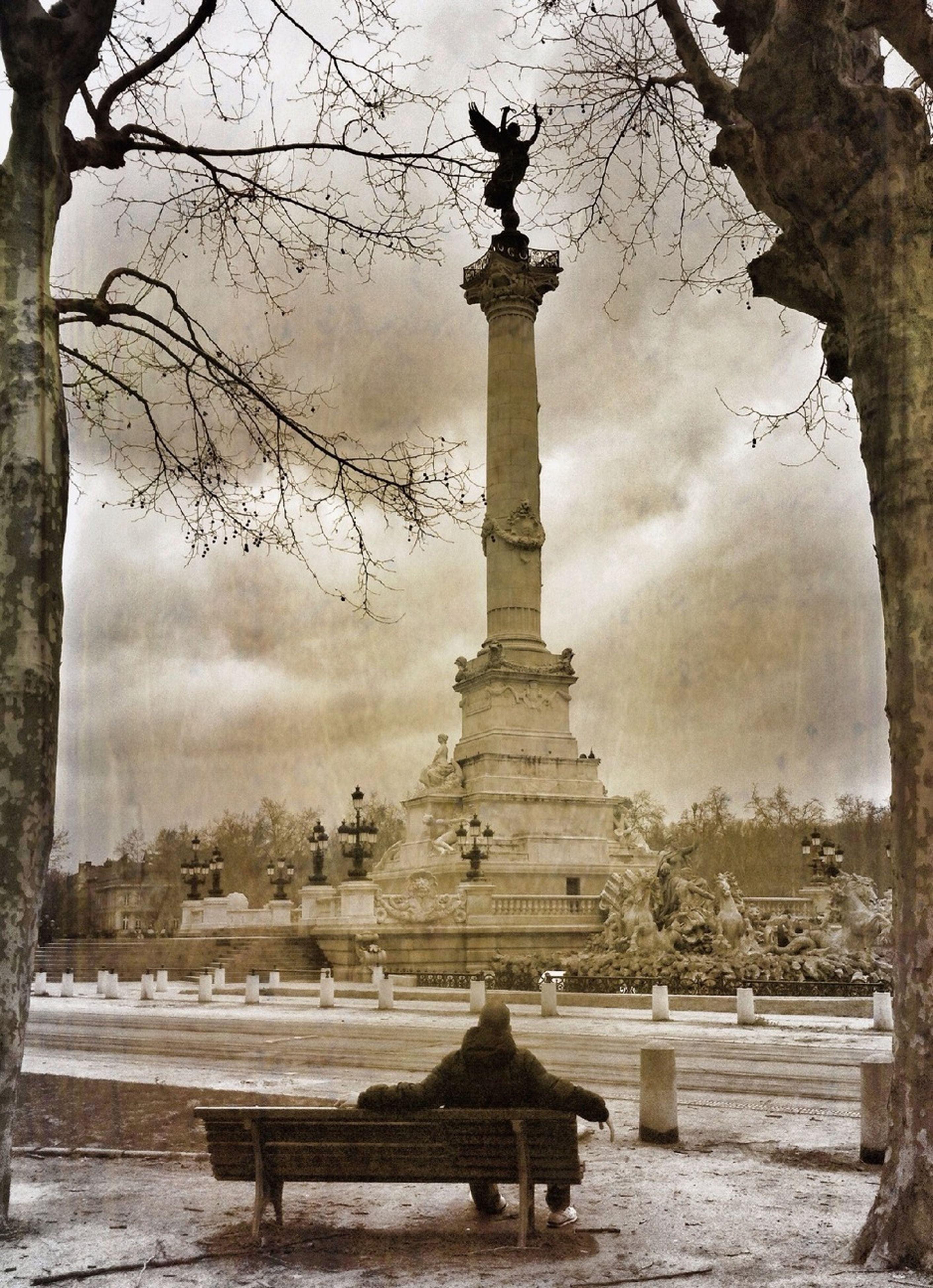 tree, sky, architecture, built structure, cloud - sky, statue, bare tree, building exterior, sculpture, travel destinations, fountain, cloudy, famous place, art and craft, tourism, history, park - man made space, art, weather, water