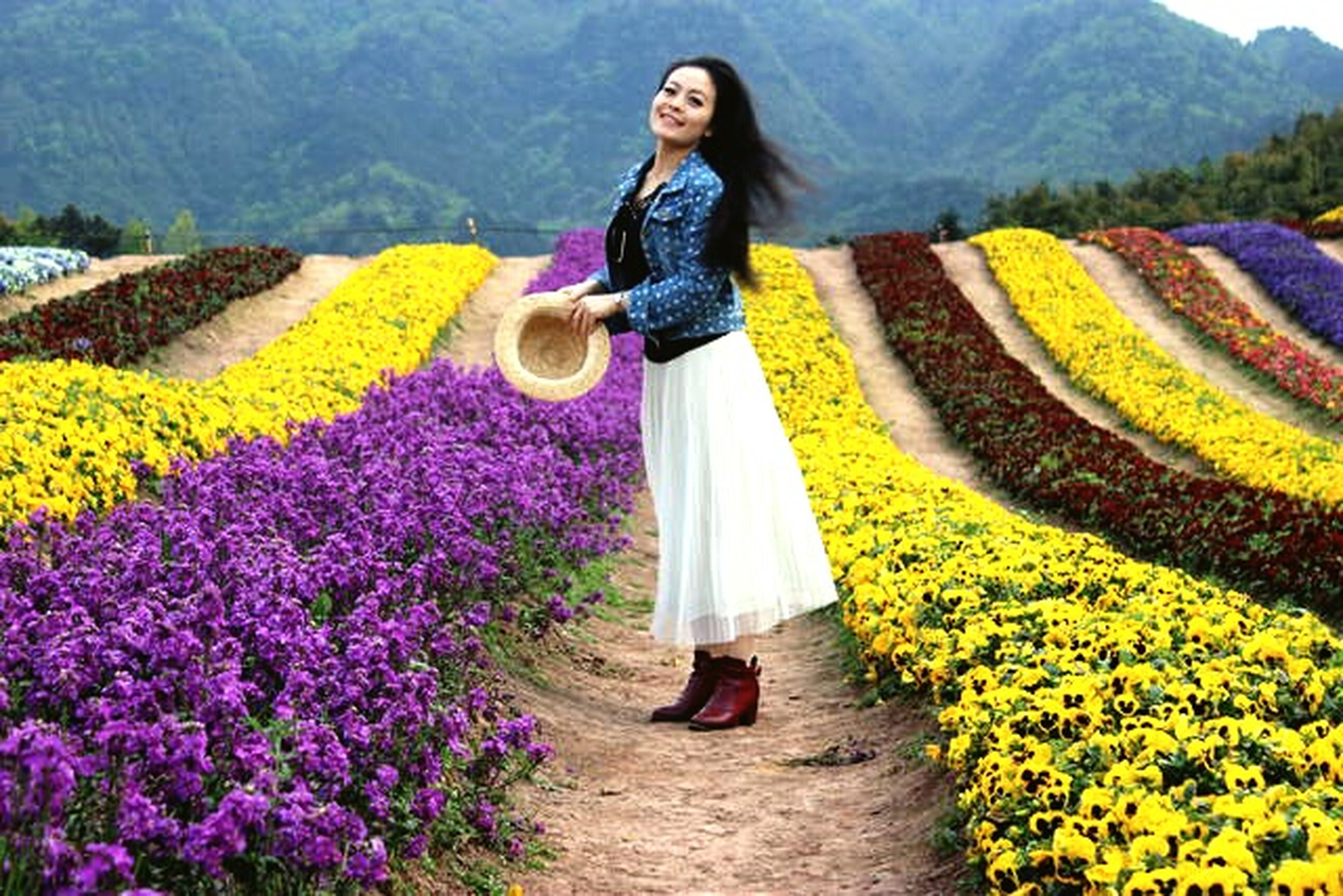 lifestyles, casual clothing, flower, leisure activity, young adult, beauty in nature, mountain, landscape, young women, growth, nature, full length, tranquil scene, field, standing, tranquility, person, scenics