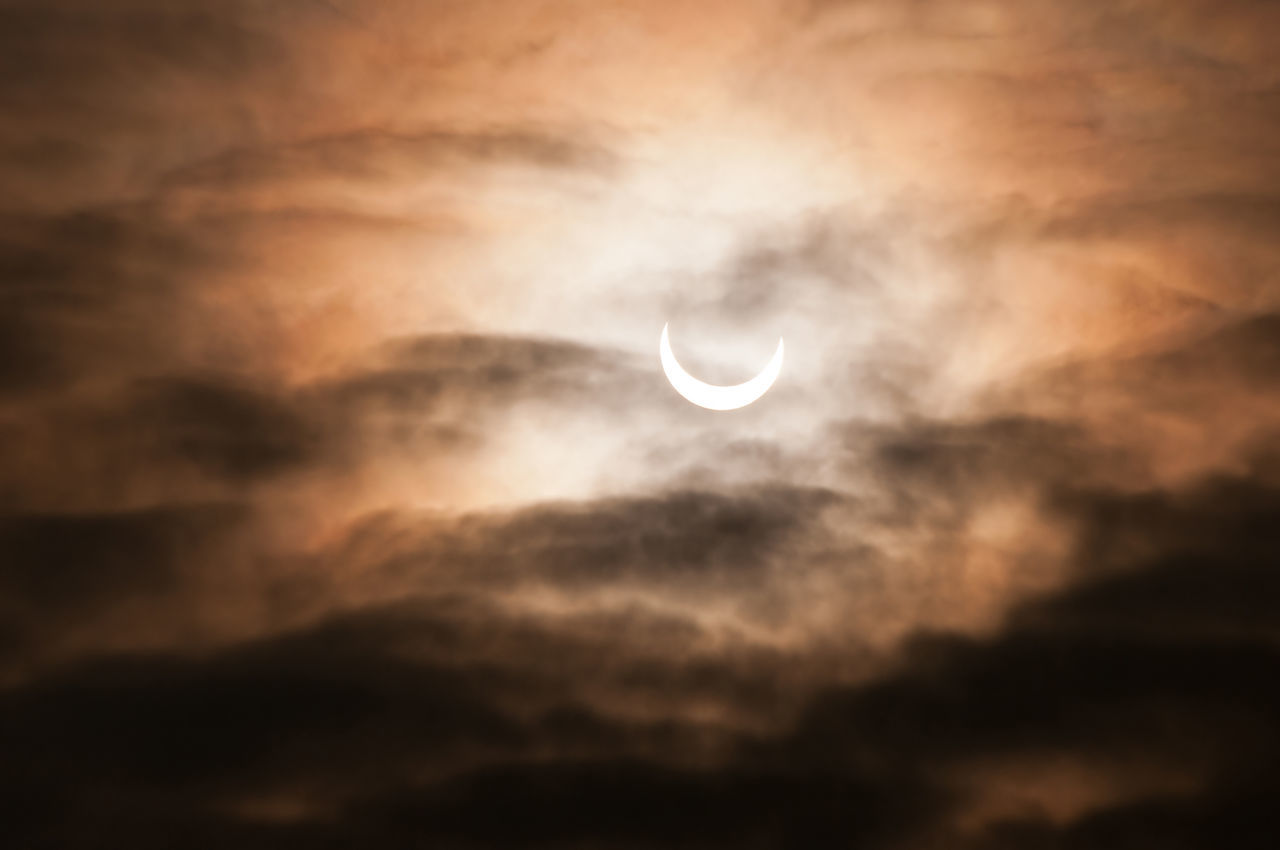 Partial solar eclipse behind clouds morning sky in Poland, horizontal orientation, nobody. Cumulus formation partially block solar eclipse, warm colors of sun. Cloud Cloud - Sky Clouds Cloudscape Day Daytime Eclipse Formation Moon Moon Nature No People Occult Partial Partially  Scenics Sky Sky And Clouds Solar Solar Eclipse Space Sun
