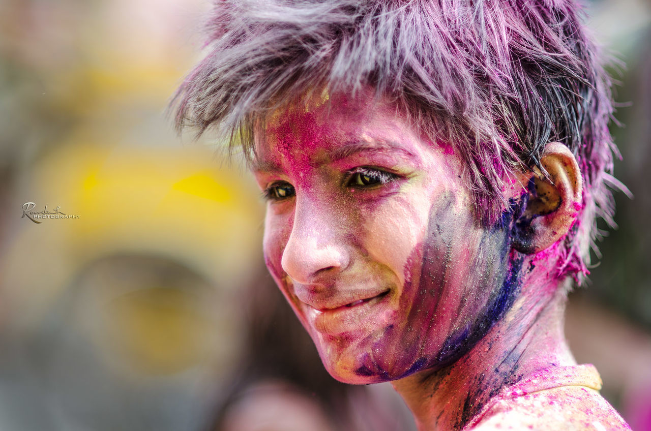 holi, celebration, traditional festival, powder paint, focus on foreground, real people, one person, headshot, happiness, cultures, face paint, lifestyles, multi colored, face powder, outdoors, looking at camera, fun, portrait, smiling, close-up, leisure activity, day, playing, young adult, talcum powder, adult, people