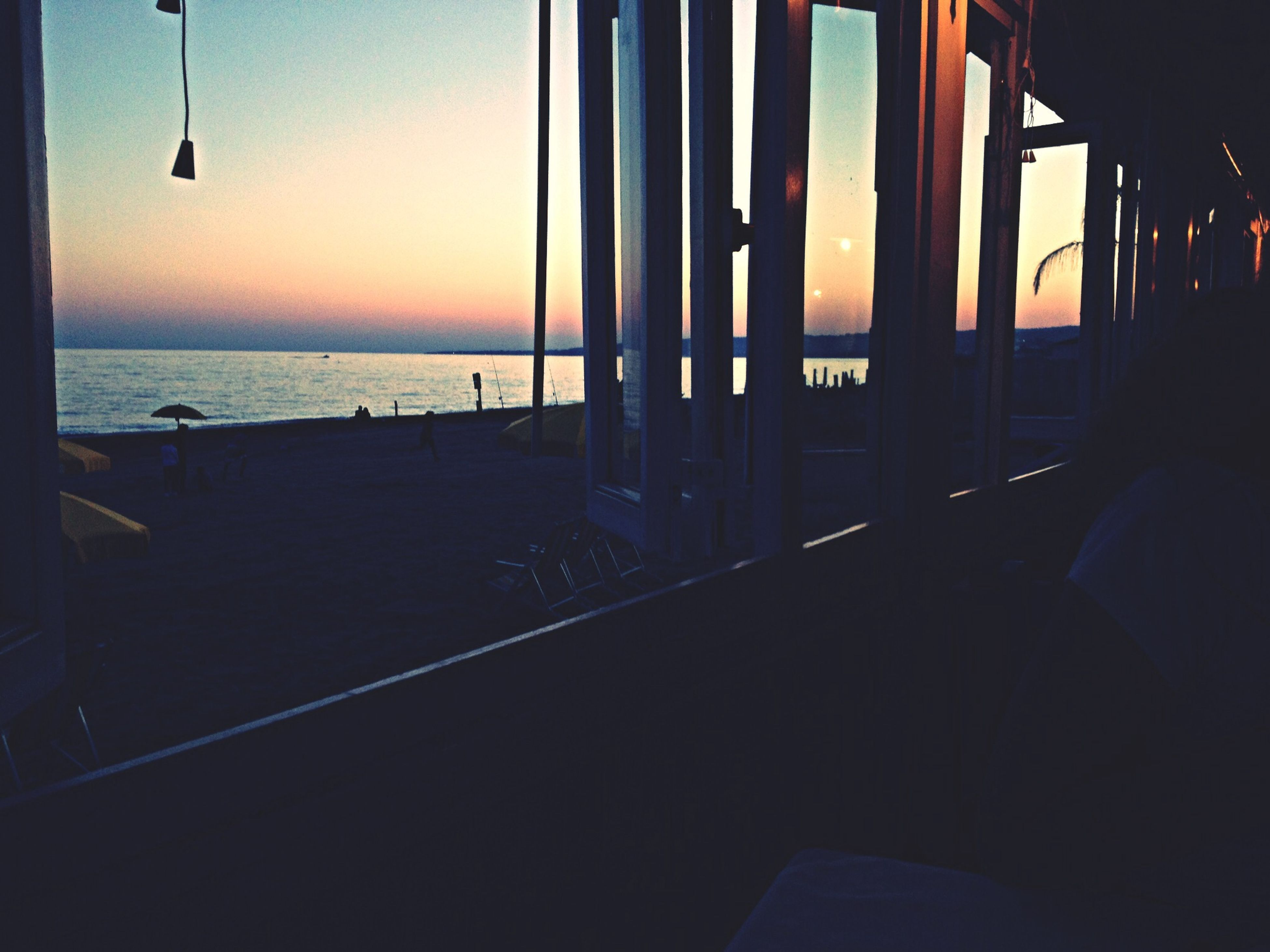 sea, sunset, water, horizon over water, sky, built structure, architecture, silhouette, orange color, beach, indoors, scenics, tranquility, dusk, beauty in nature, tranquil scene, nature, window, reflection, idyllic