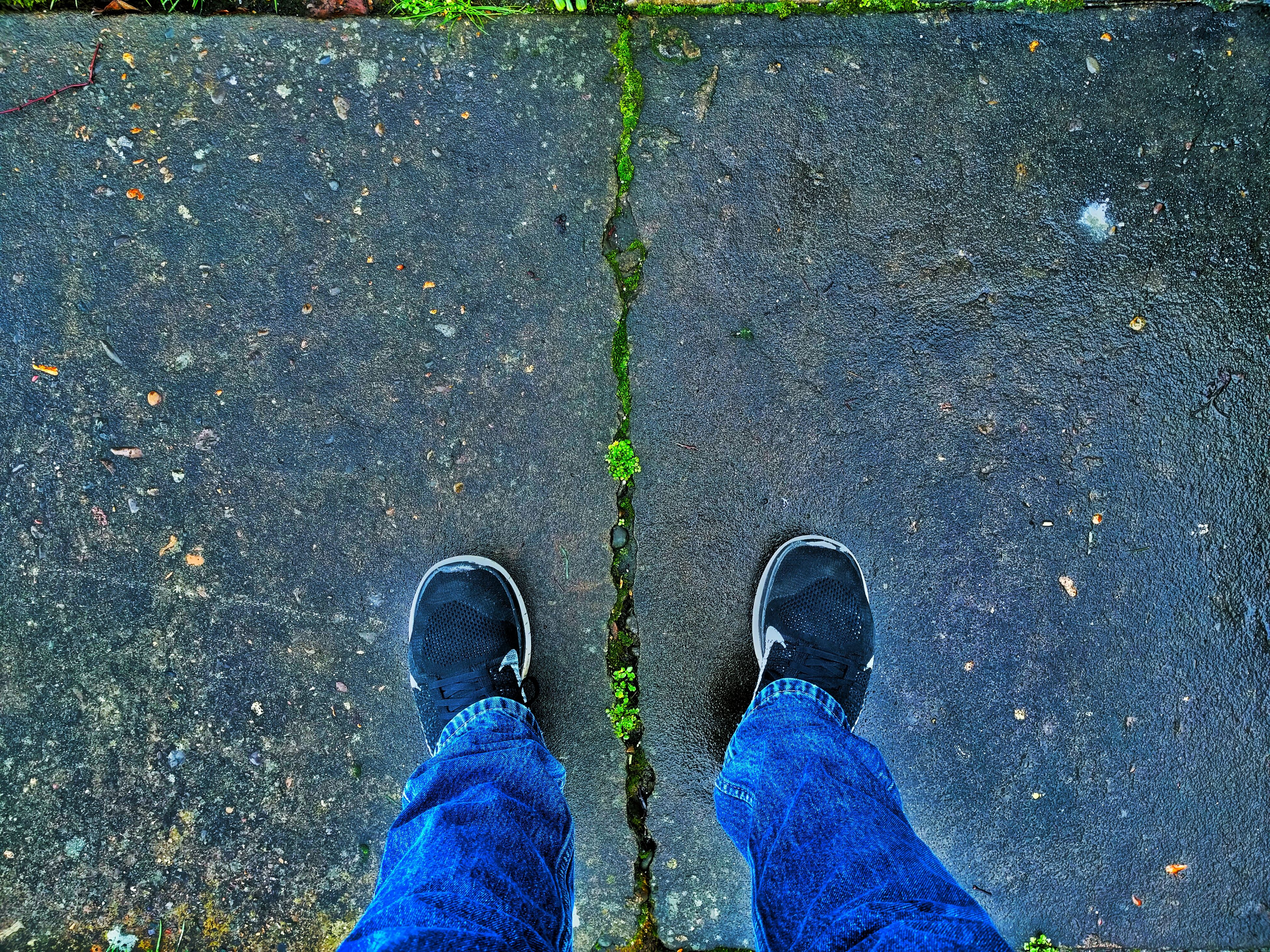 low section, person, shoe, personal perspective, standing, street, lifestyles, high angle view, road, men, leisure activity, jeans, asphalt, leaf, blue, unrecognizable person, day