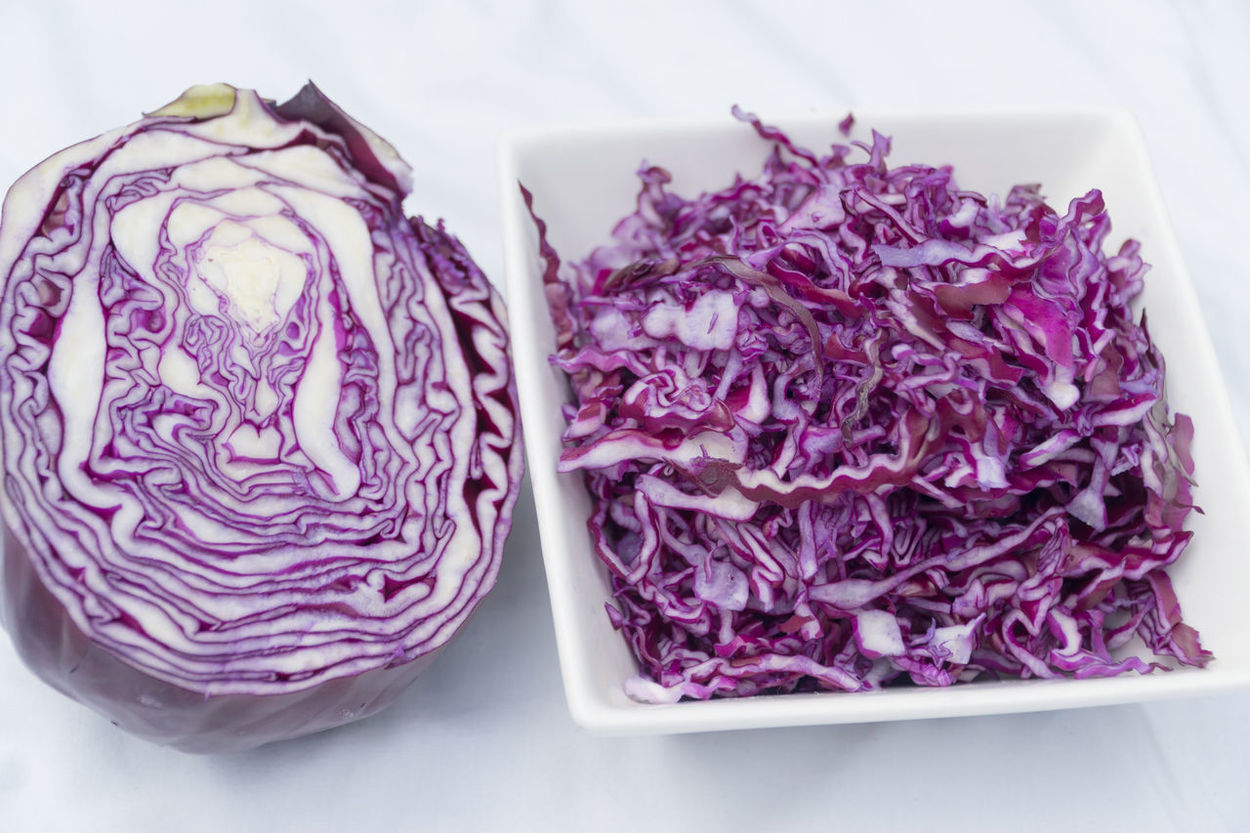 Red cabage shredded in a display dish, and half a red cabage for your perusal. Daytime Photography Display Food Red Cabage Shredded Cabage Table Vegetables White Dish